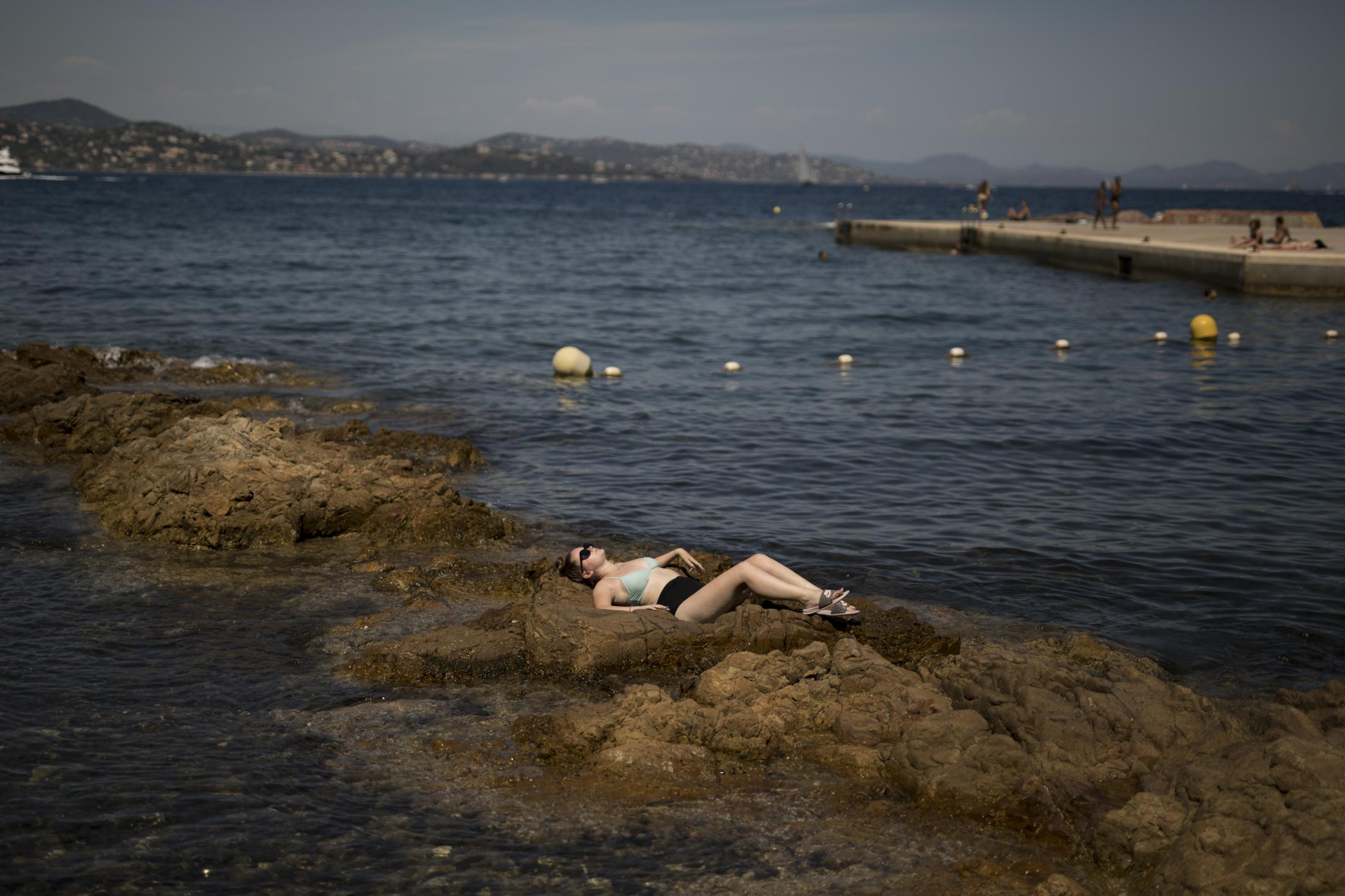 A woman sunbathes on the rocks in Saint-Tropez, southern France, Saturday Aug 8, 2020. The glamorous French Riviera resort of Saint-Tropez is requiring face masks outdoors starting Saturday, threatening to sober the mood in a place renowned for high-end, free-wheeling summer beach parties. (AP Photo/Daniel Cole)