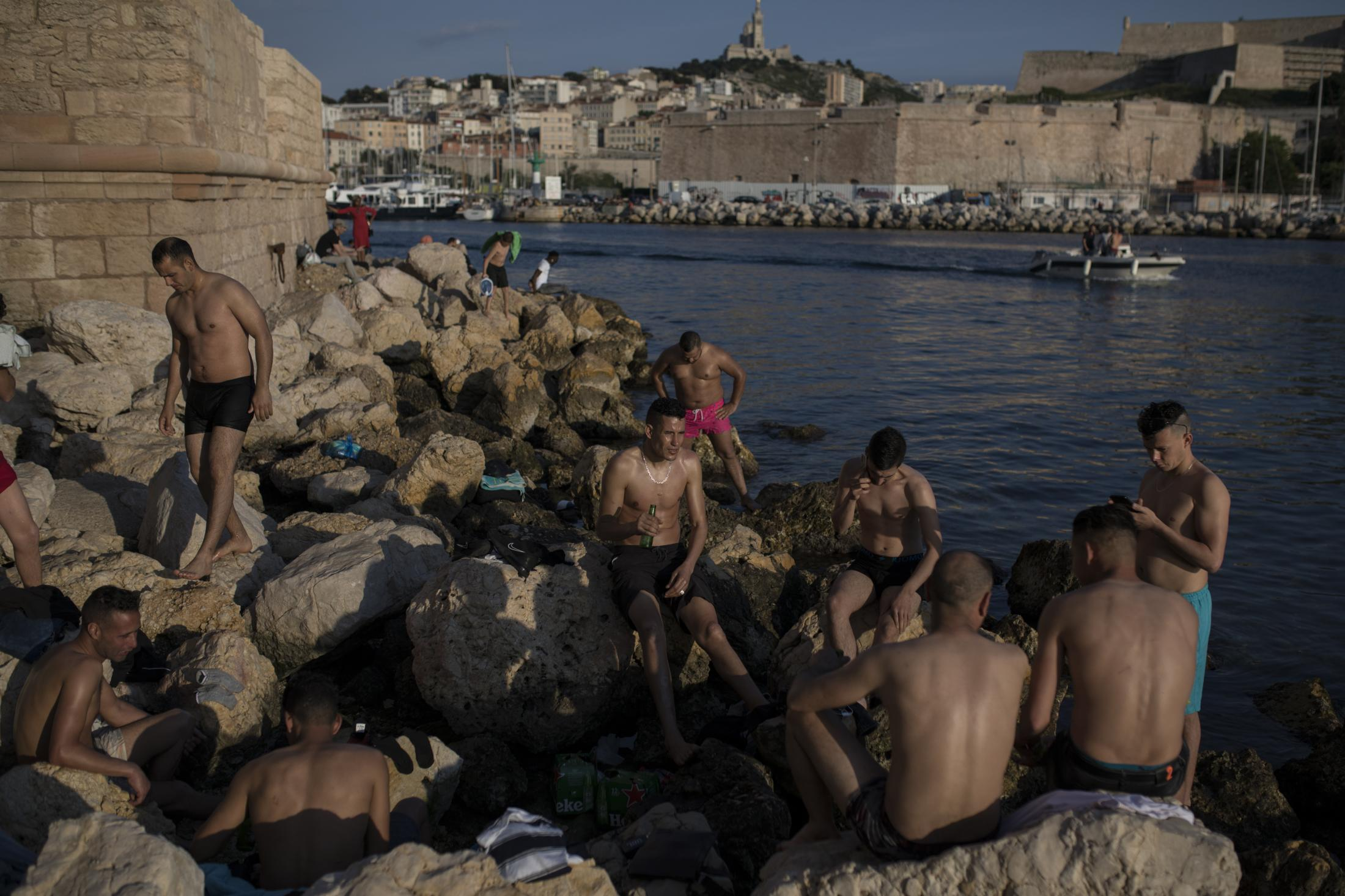 Sunbathers enjoy the sunset at the entrance to Marseille�s Old Port in southern France, Tuesday, May 26, 2020 as France gradually lifts its COVID-19 lockdown. (AP Photo/Daniel Cole)