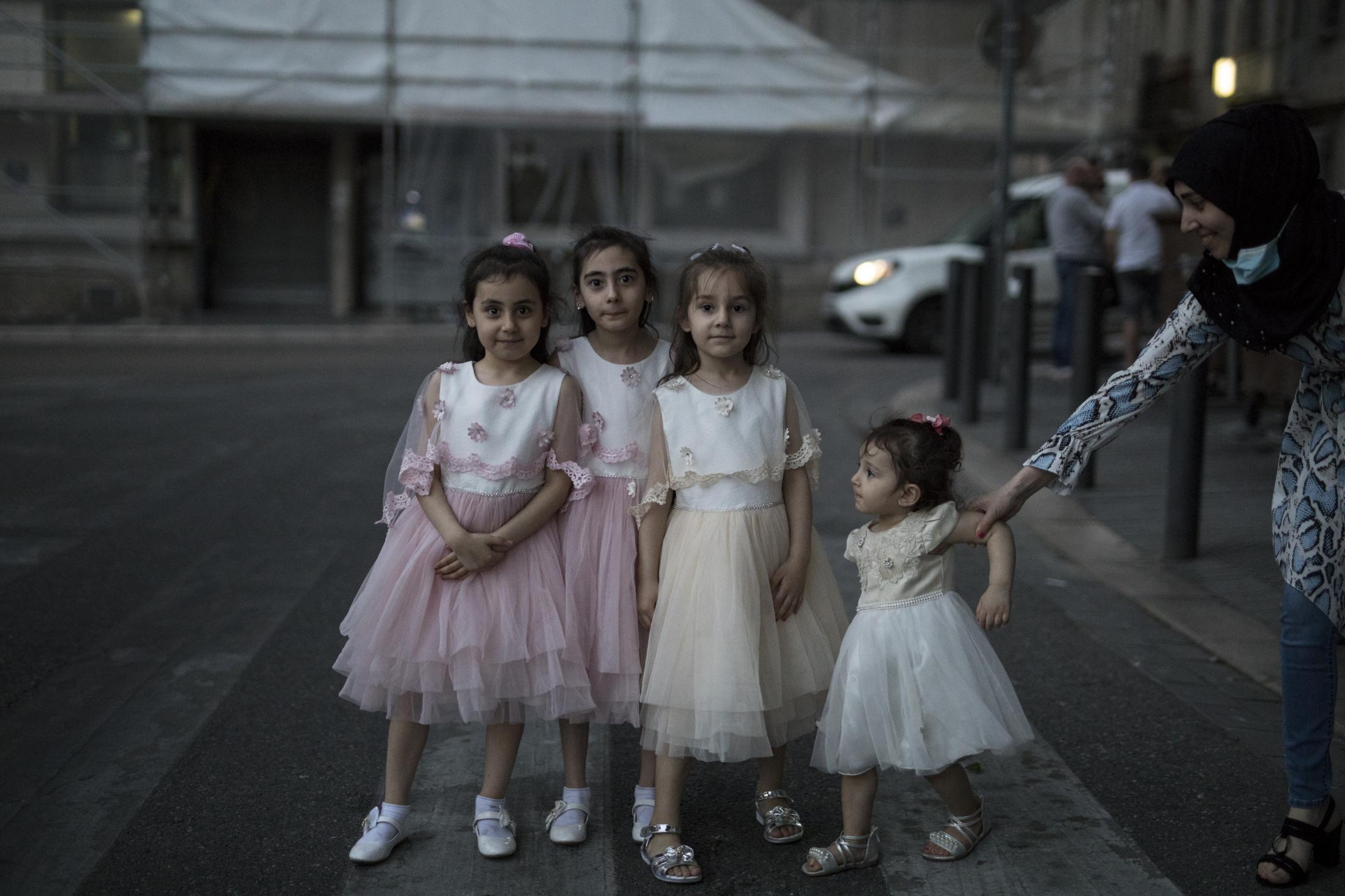 A mother poses her children wearing matching dresses in the street during an evening walk in Marseille, southern France, Tuesday, May 26, 2020 as France gradually lifts its COVID-19 lockdown. (AP Photo/Daniel Cole)