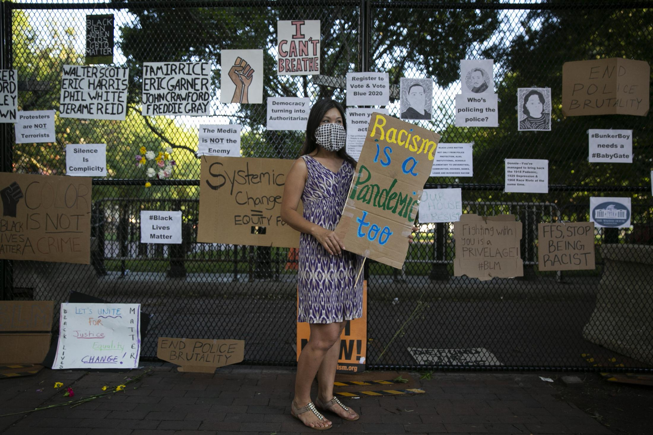 """Washington, D.C. resident Sara gets up at eight in the morning and puts up signs on the security fence surrounding the White House. She makes a sign which says, """"Racism is a pandemic too"""", as a response to both the ongoing series of protests against the killing of George Floyd and hate crimes towards Asians for being blamed for the spread of coronavirus. """"I was never protesting until the protesters were forced to leave,"""" Sara says, """"That to me is the First Amendment right to be heard."""""""