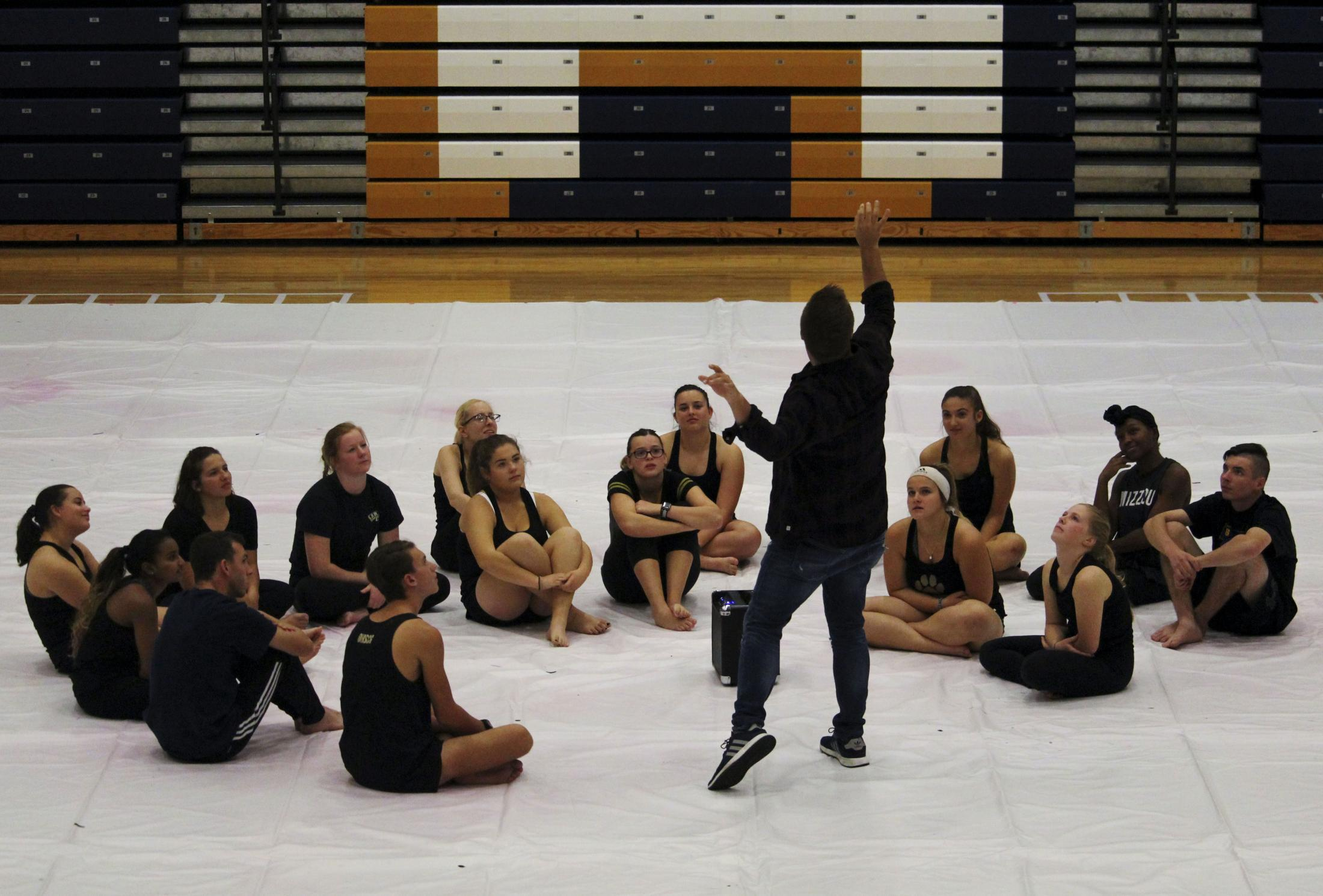 """Zachary Barber, design coach for Ionic Independent, demonstrates his vision for its 2020 show during the first meeting November 1, 2020, at Battle High School in Columbia, Missouri. On this day, members also learned that their show would be titled 'The Artistry of Motif' and follows the ideas of motifs and synchronicity in visuals, attitudes and routine. Barber discussed how he also wanted to follow the """"motif"""" of the team where each year the show is something simple but unique to the team members of that season."""