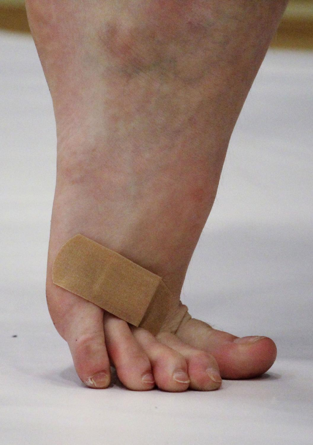 """Stephens College freshman Lauren Buzzell returns to tendu, a ballet position, after applying a bandage November 3, 2019, at Battle High School in Columbia, Missouri. Buzzell had been tossing a flag, which landed on her foot, breaking the skin. She quickly ran off to apply a bandage before returning to the floor to continue the practice without disturbing anyone. Part of being a team in the guard is rushing through mending injuries so that there is no chance of desynchronization. """"We all have to be together"""" is a motto both the coaches and the teammates call out during practice."""