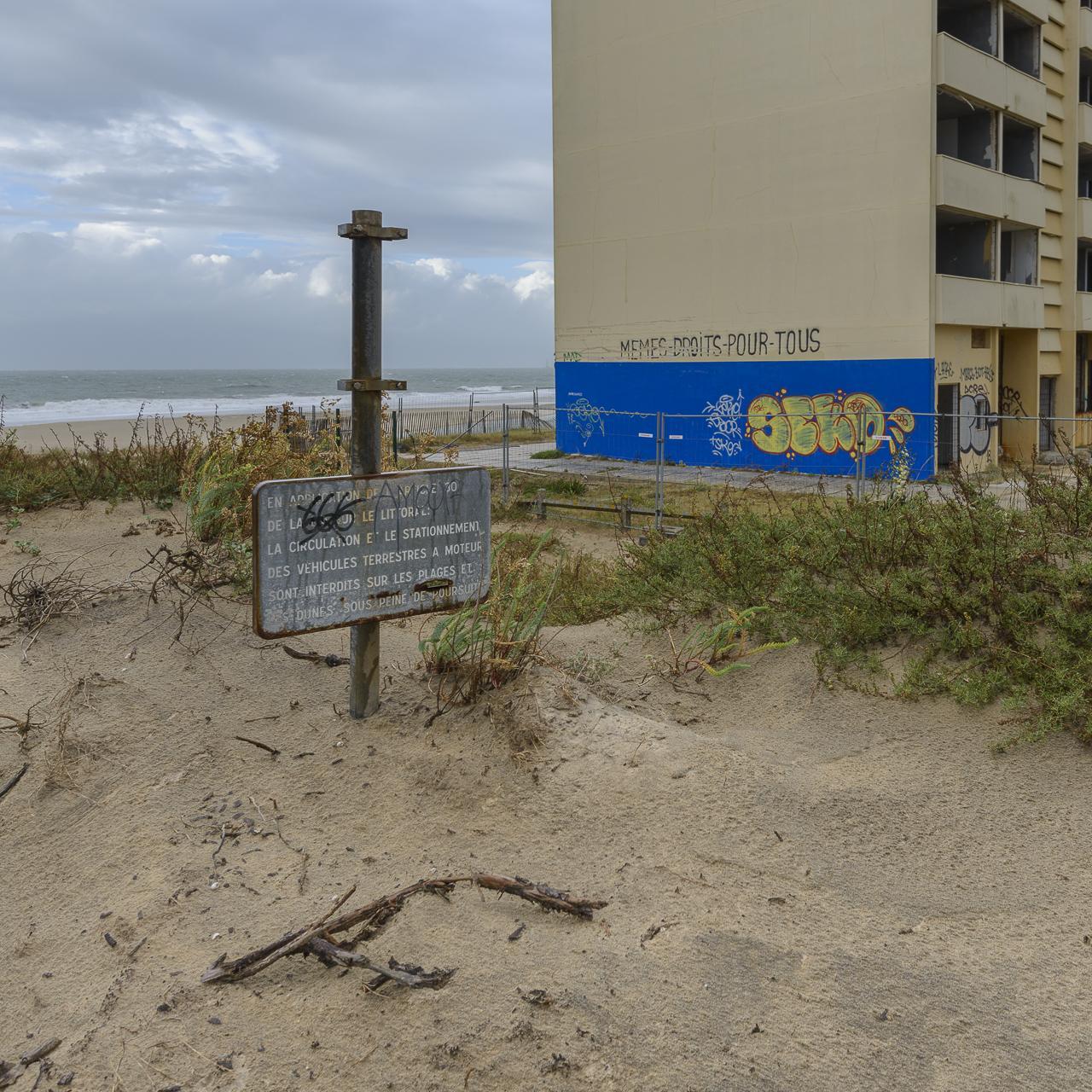 Le panneau d'accès à l'ancien chemin vers la plage qui longeait l'immeuble Le Signal est enseveli sous le sable en raison du recul de la dune.