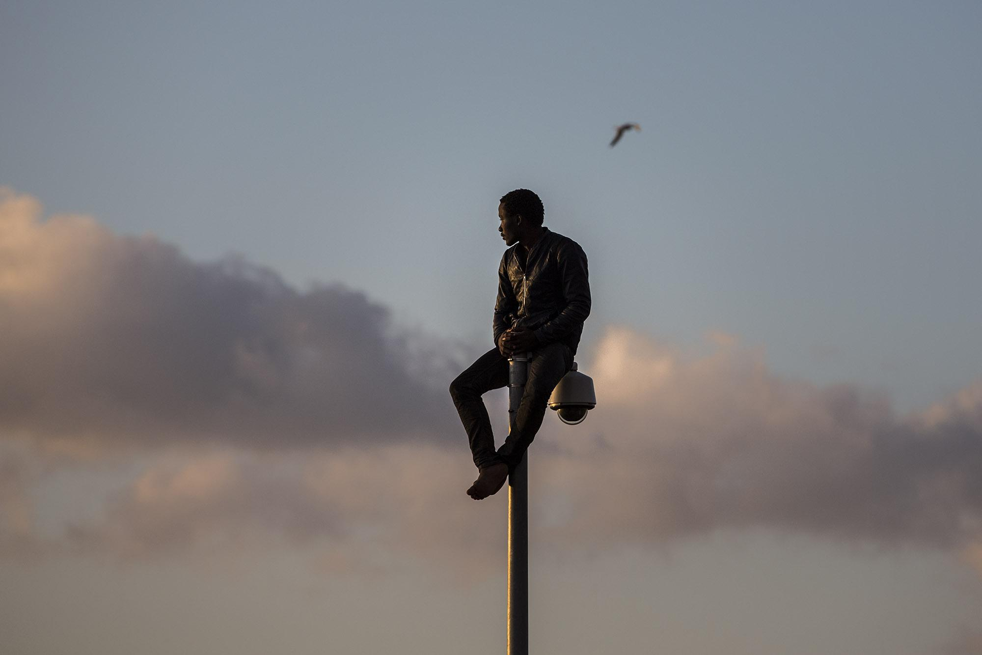 A sub-Saharan migrant sits on top of a pole set in a metallic fence that divides Morocco and the Spanish enclave of Melilla. He was pushedback to Morroco by the Spanish Guardia Civil after spending hours on top of that pole inside Spanish soil, Wednesday, May 28, 2014. More than 400 African migrants managed to jump the barbed-wire border fence in SpainÌs North African enclave of Melilla, hundreds of others were blocked and beaten back by Moroccan police while the rest were pushedback by the Spanish Guardia Civil. During the pre-dawn border storming, cries of pain and noises of people being hit could be heard as police from both sides tried to prevent dozens of the sub-Saharan migrants from entering the city from Morocco. (© Santi Palacios)