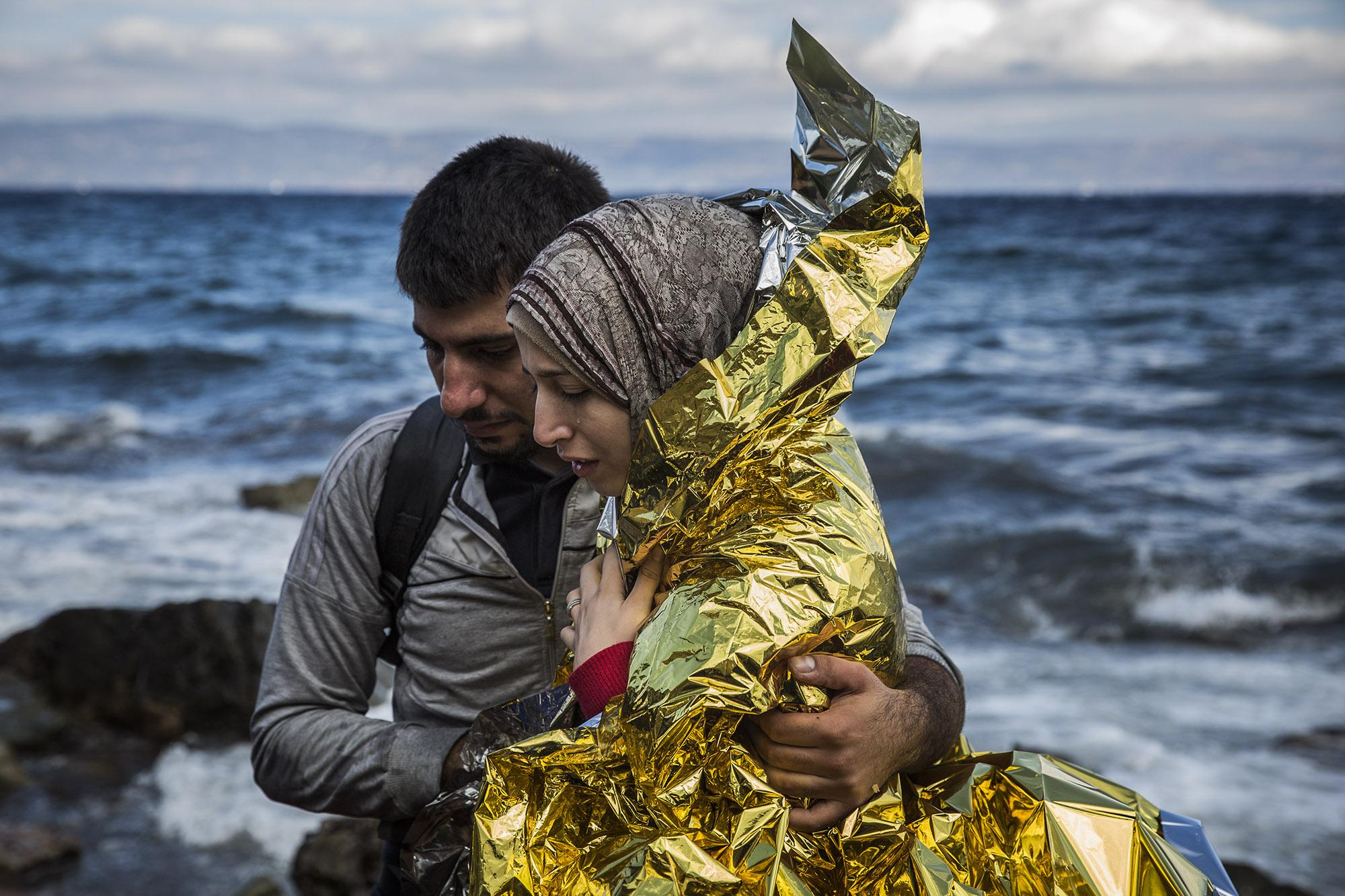 A couple embraces right after after crossing the Aegean sea aboard a rubber boat, with other refugees from the Middle East, from the Turkish coast to the northeastern Greek island of Lesbos, on Wednesday, Sept. 30, 2015. The International Organization for Migration said that week a record number of people had crossed the Mediterranean into Europe, topping a half a million, with some 388,000 entering via Greece. (© Santi Palacios)