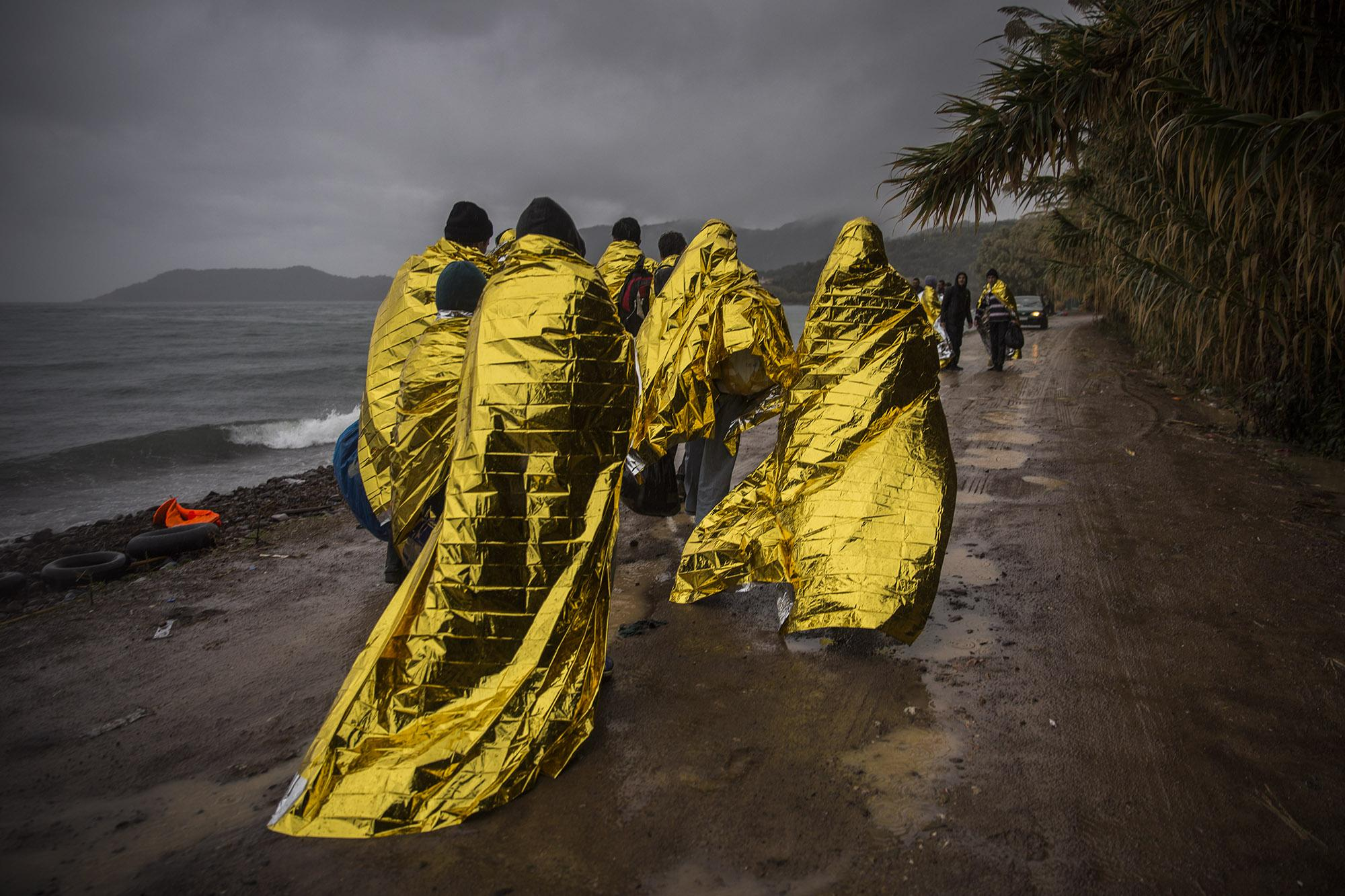 Men cover themselves with thermal blankets after crossing the Aegean Sea aboard a rubber boat from the Turkish coast to the northern coast of the Greek island of Lesbos, facing extremely hard weather conditions at sea, on Friday, Oct. 23, 2015. The International Office for Migration said over that week Greece experienced the largest single weekly influx of migrants and refugees in 2015, at an average of some 9,600 per day. (© Santi Palacios)