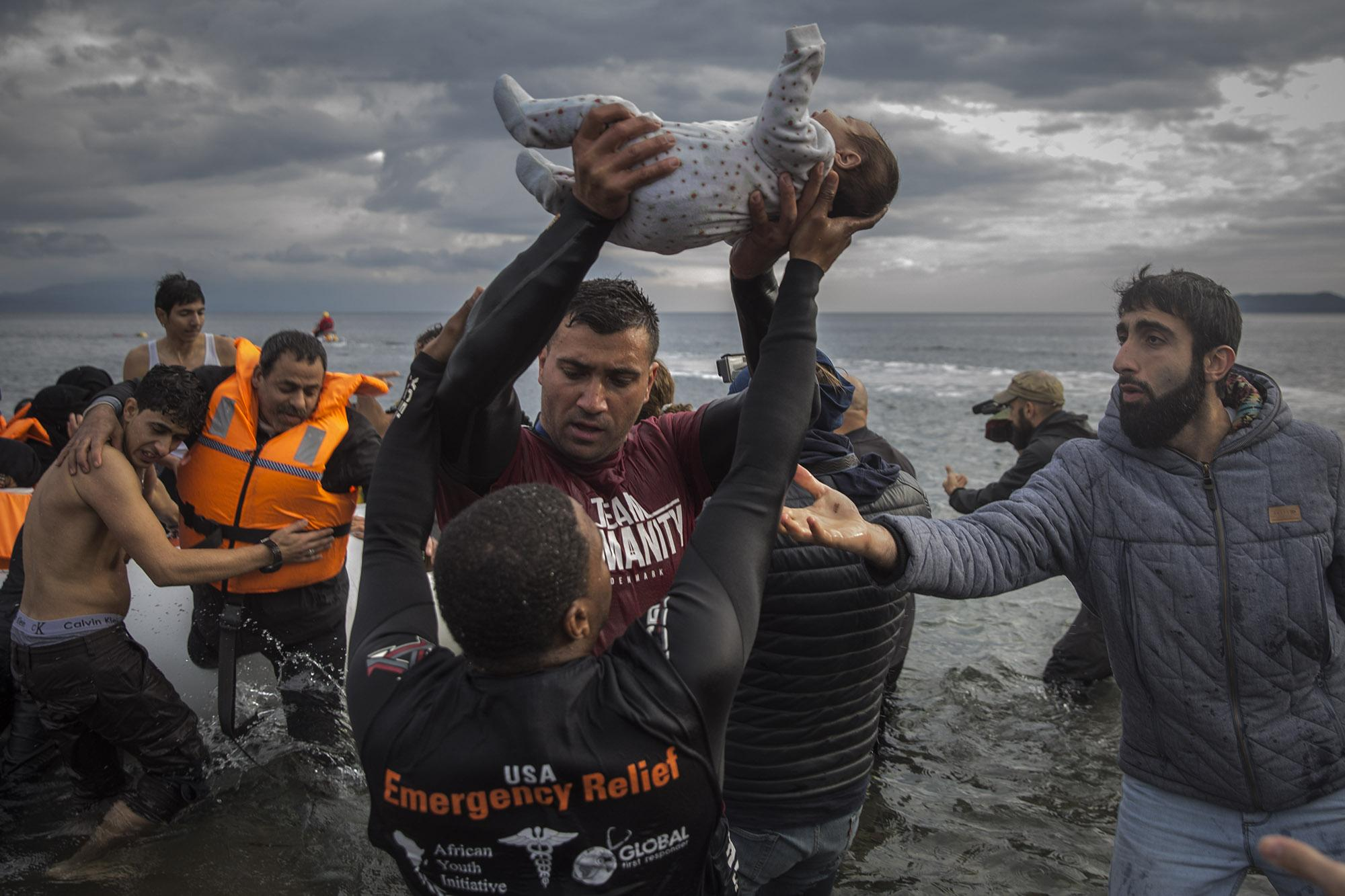 A volunteer holds up a baby as other tries to help him awkwardly as migrants and refugees disembark from a dinghy after their arrival from the Turkish coast to the Greek island of Lesbos, Wednesday, Nov. 25, 2015. The volunteer holding the baby is Salam Aldeen, who was absurdly acused of human traficking by Greek coastguards in January 2016 while helping on migrants rescue operations in the island of Lesbos. (© Santi Palacios)