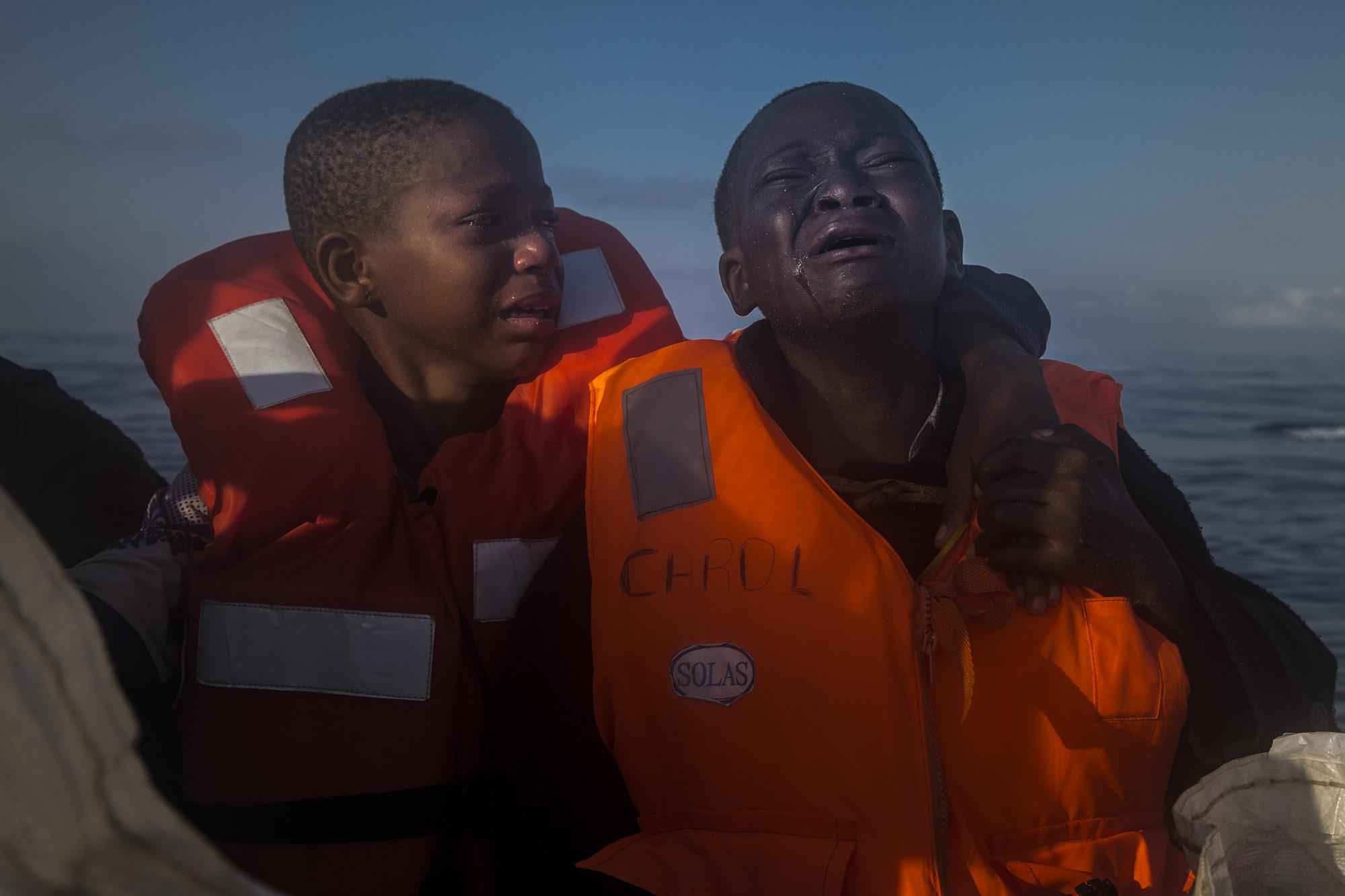 A 11-year-old girl from Nigeria, (left), who said her mother died in Libya, cries next to her 10-year-old brother, aboard a rescue boat assisted by an NGO, after sailing for hours aboard an overcrowded rubber boat with other refugees and migrants, during a rescue operation on the Mediterranean Sea, about 23 kilometers (14 miles) north of Sabratha, Libya, on Thursday, July 28, 2016. (© Santi Palacios)