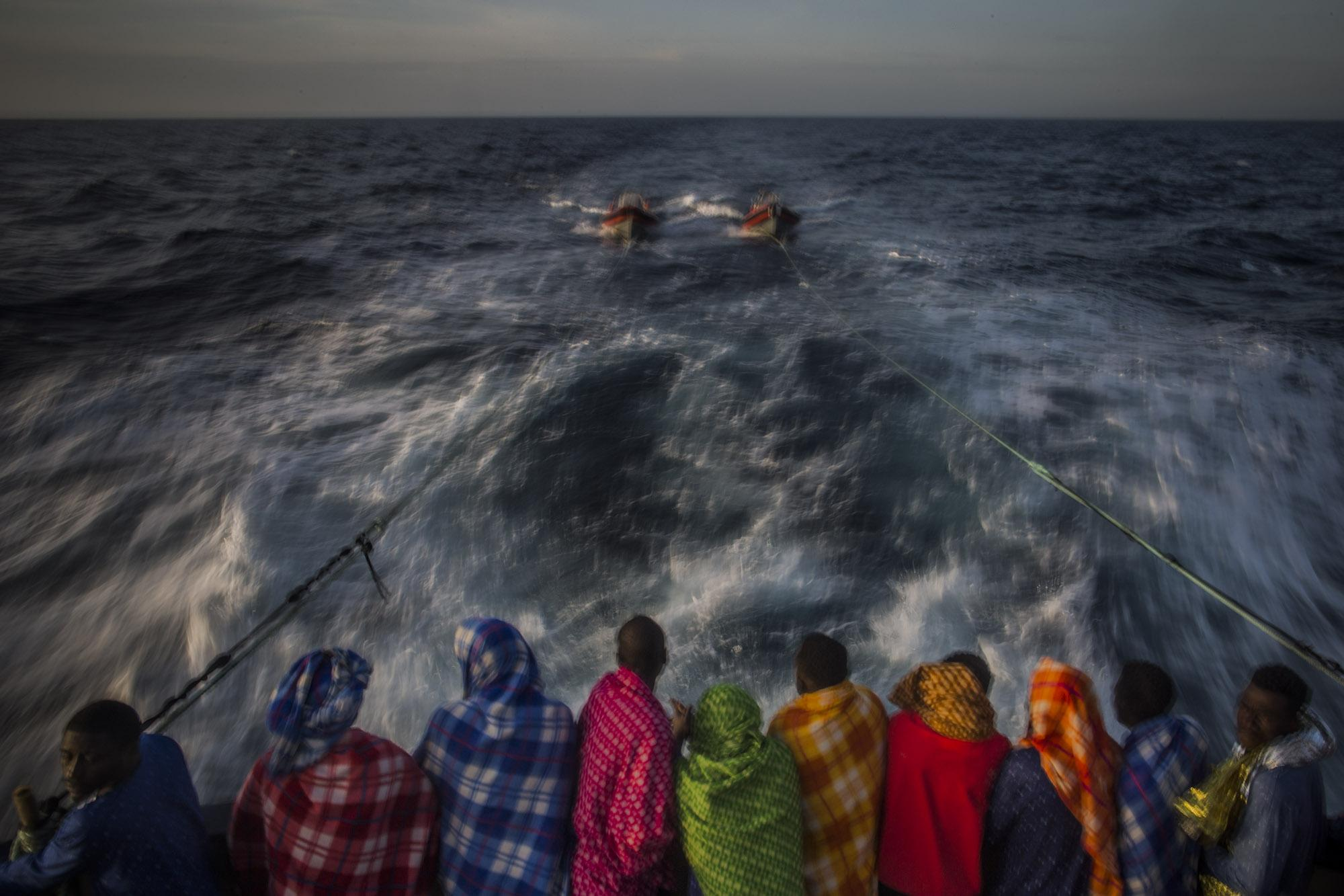 Migrants from different African nationalities rest aboard a Spanish NGO Open Arms rescue ship, as the vessel heads to the Italian island of Lampedusa, early Sunday, March 5, 2017. When I shot this pictture, a team of aid workers had already rescued more than 800 people, during a 2-weeks rescue mission in international waters, off the Libyan coast, as thousands of migrants, mostly Africans but also from Middle East and South Asia, were leaving Libya and trying to reach Europe aboard overcrowded and precarious rubber and wooden boats that could had never crossed the Mediterranean successfully. (© Santi Palacios)