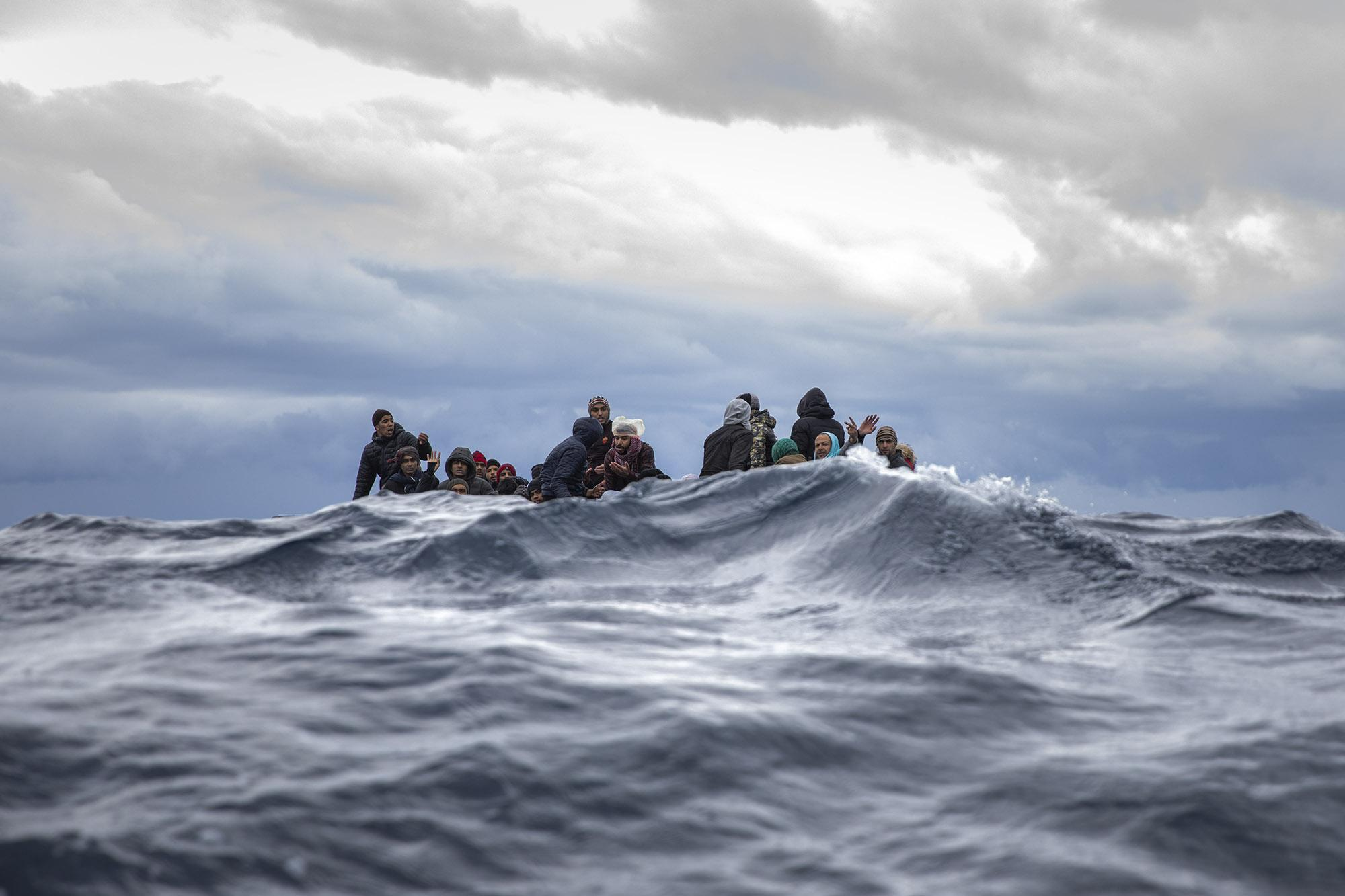 Moroccans and Bangladeshis wait on an overcrowded wooden boat, as aid workers of the Spanish NGO Open Arms approached them off the Libyan coast, Friday, Jan. 10, 2020. (© Santi Palacios)
