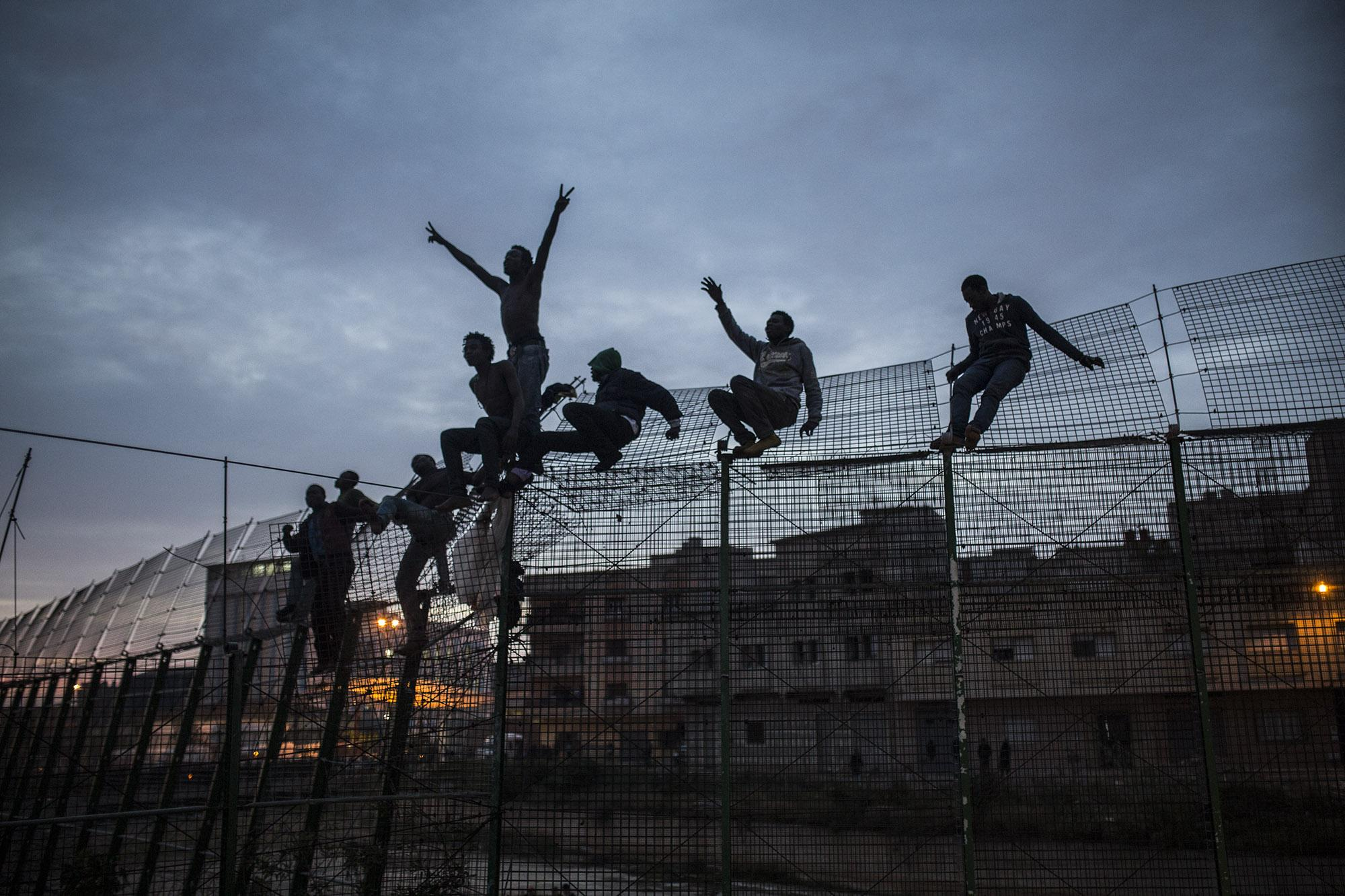 Sub-Saharan migrants climb over a metallic fence that divides Morocco and the Spanish enclave of Melilla on Friday March 28, 2014. Several hundred African migrants tried to cross barbed-wire border fences to enter the Spanish enclave of Melilla from Morocco but most were blocked by Moroccan police or pushedback by the Spanish Guardia Civil as a handful managed to remain in European soil. In early 2014 thousands of migrants seeking a better life who couldn't afoard to pay to cross the Mediterranean sea aboard a rubber raft to get to Europe, were living illegally in the forests of north Morocco hoping they could enter Melilla and Spain's other north African coastal enclave, Ceuta. (© Santi Palacios)