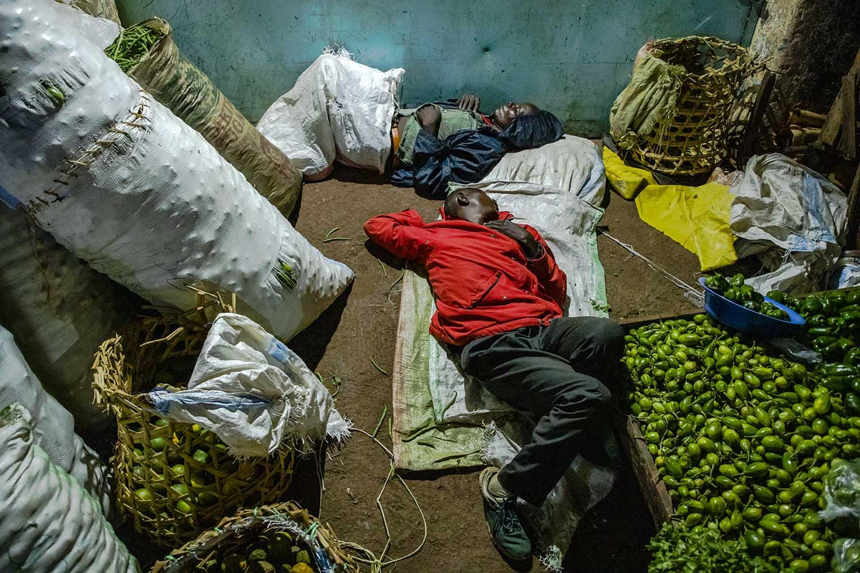 Vendors sleeping next to their stock at Nakawa Market in Kampala.