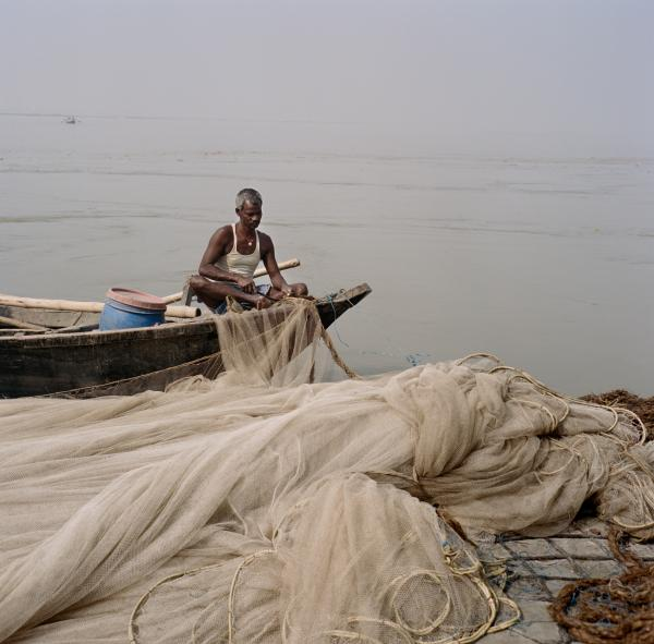 Vinod Sahni along with his family members and helpers prepare for an evening of fishing out along the Ganges. They spent several hours this day repairing their plastic fishing net before departing from the village of Rasalpur, Dharnipatti, Bihar on Nov. 14, 2019. Taken on assignment for National Geographic