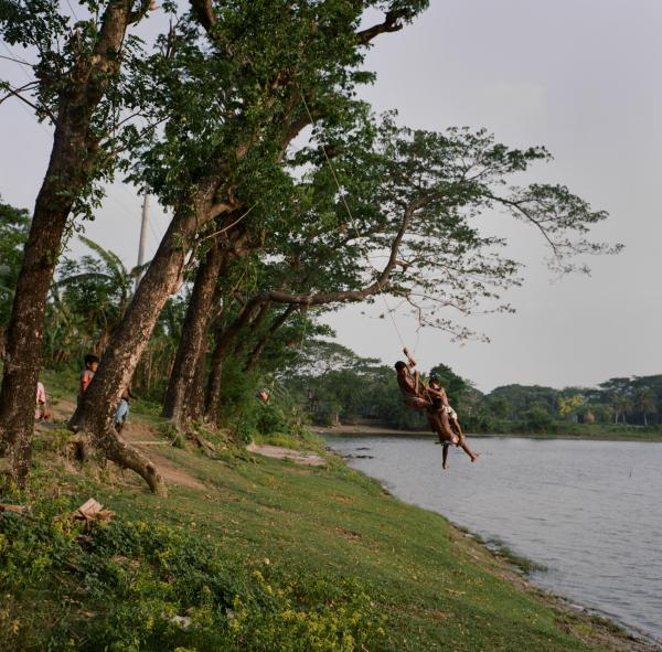 """Young boys play near a pond close the Meghna River on May 14, 2019. Taken on assignment for National Geographic's """"Sea to Source: Ganges"""" expedition. Through the expedition, the international, all-female team of scientists are working with National Geographic and international partners to scientifically document plastic waste in the Ganges watershed and support holistic and inclusive solutions."""