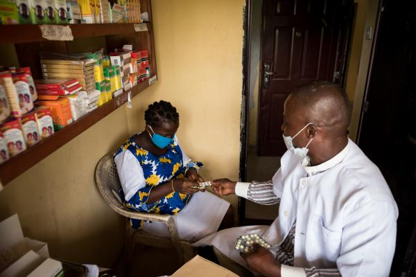 A pharmacy technician hands over a prescribed drugs to a patient.
