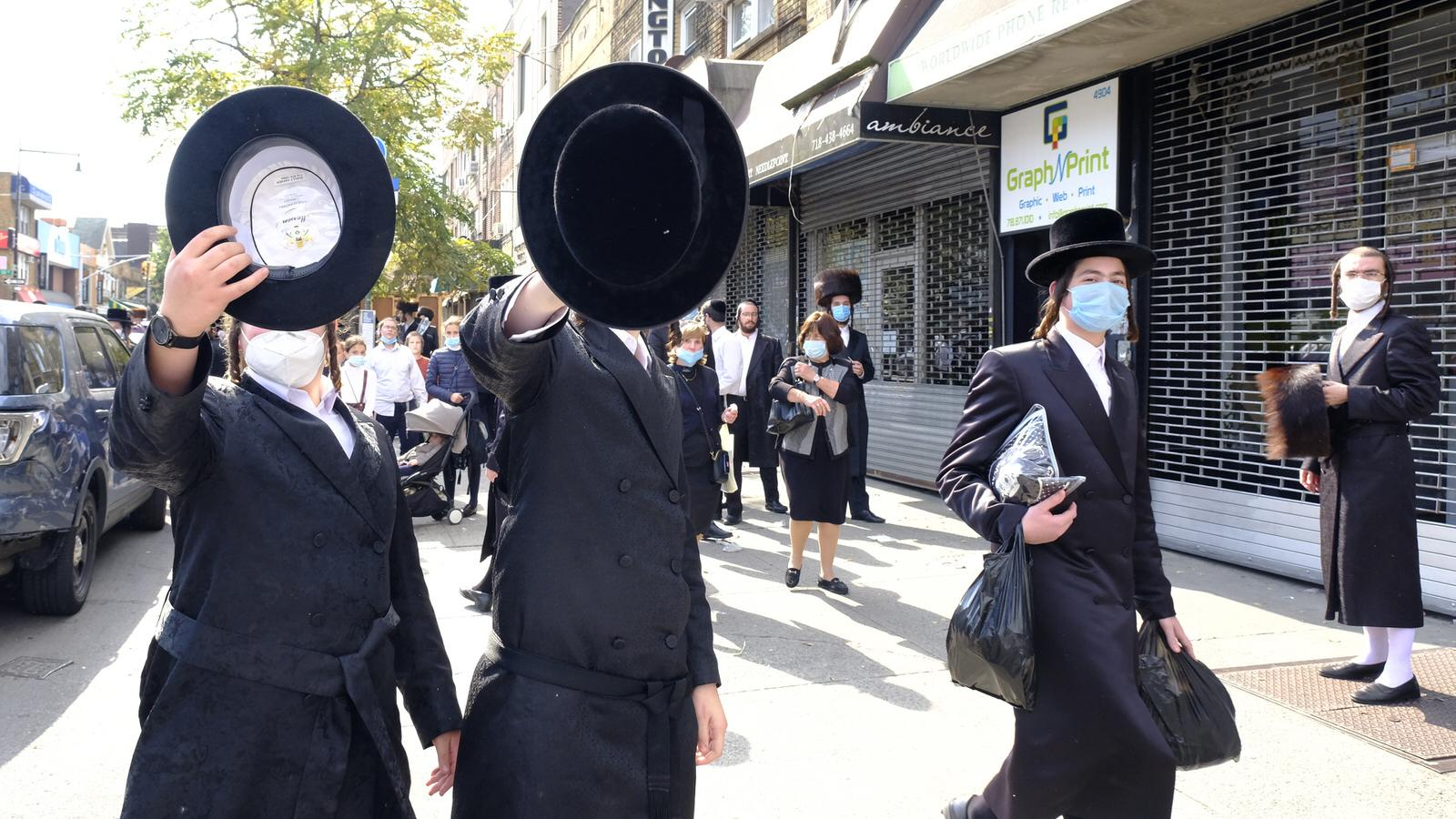 Brooklyn - October 7, 2020 - A group of Orthodox Jewish teenagers some wearing facial mask tries to block this photographer from taking pictures on 13th Avenue near 49th Street in the Borough Park section of Brooklyn Wednesday afternoon. NYPD 66th Precinct Officers showed at the scene but did not ticket or warned the mask less members of the crowd. New Yorkers who hold mass gatherings will be fined up to $15,000 per day, Mayor de Blasio announced Wednesday, the latest step aimed at cracking down on an alarming spike in COVID cases in parts of Brooklyn and Queens. (Luiz C. Ribeiro for New York Daily News)