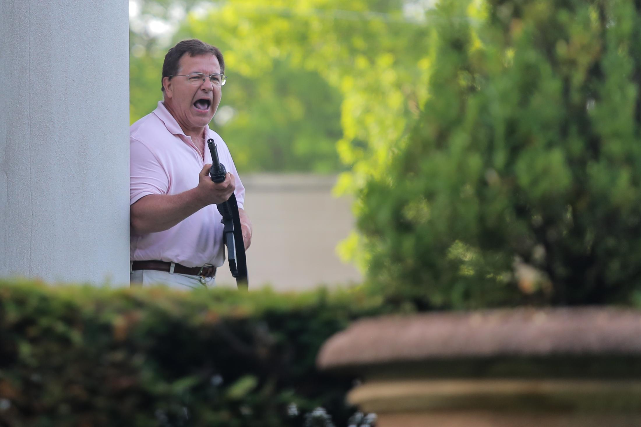 Mark McCloskey waves his AR-15 rifle over protesters who marched onto Portland Place in front of the house where he and his wife Patricia live on June 28, 2020, in St. Louis. A group of around 150 protesters broke away from a larger group and walked through a gate where they were confronted by the armed couple.