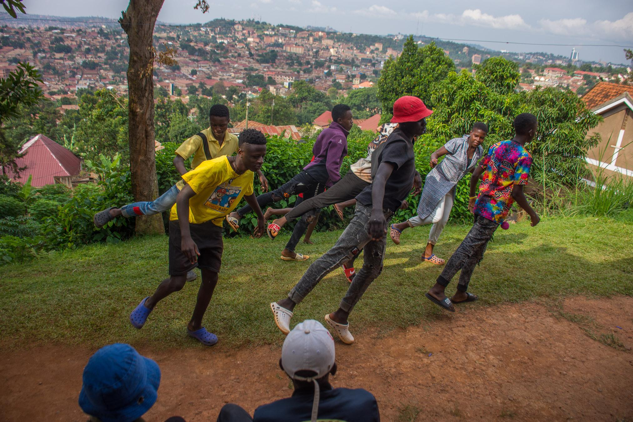 Step Code Crew members pulling off a move as colleagues look on at one of their member's home on Lubya Hill overlooking the city suburbs of Kasubi, Kawala, Kololo and Nakasero Hills..