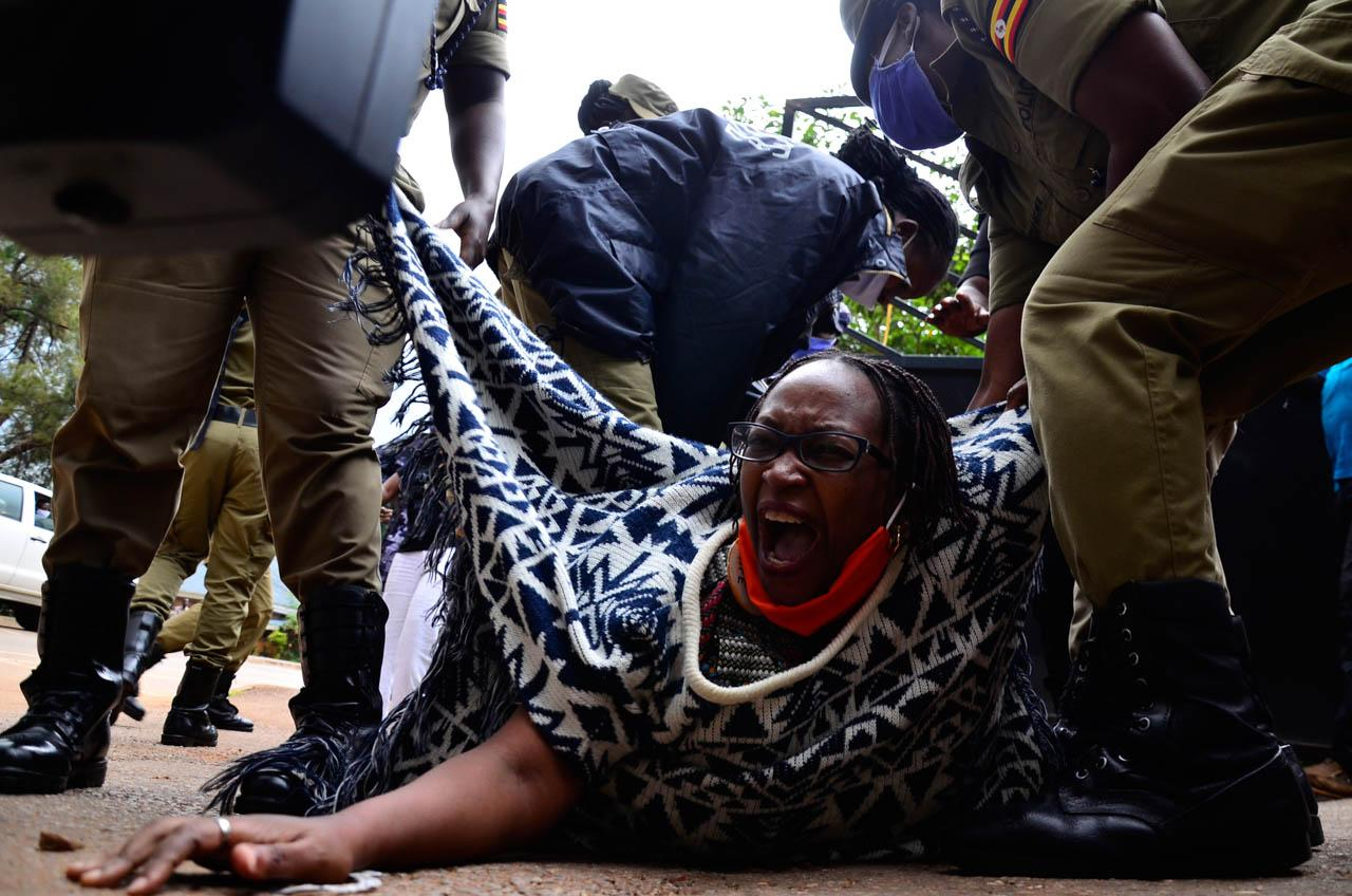 Abubaker Lubowa  1st Place, News  Mask Off  Female police officers drag prominent Ugandan academic Dr. Stella Nyanzi to a waiting police van near Buganda Road court in Ugandans capital, Kampala, during a protest against the conditions of the government-mandated nationwide lockdown. The protesters were calling for removal of a number of restrictions put in place to prevent the spread of COVID-19. Dr. Nyanzi said that the prevailing measures have created an apartheid state and occasioned avoidable suffering upon many Ugandans, especially women, low-income earners and ordinary citizens. Dr. Nyanzi was arrested with four others and detained at Central police station in Kampala.