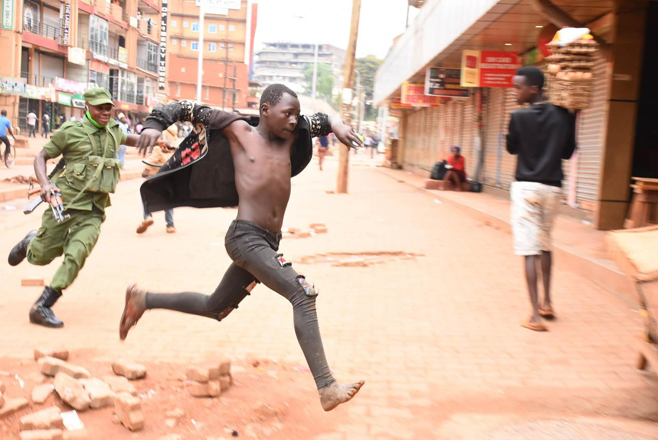 Alex Esagala  2nd Place, News  Lockdown Enforcement  A Local Defence Unit soldier runs after a man found selling masks and hand sanitizers on the street in downtown Kampala on March 26, 2020. The soldiers had been deployed on streets across the country to disperse crowds and ensure that guidelines to contain the spread of the Covid-19 pandemic were being followed. The previous day, President Museveni had announced a number of preventive measures. One of them was that street vendors were to suspend their activities unless selling food.