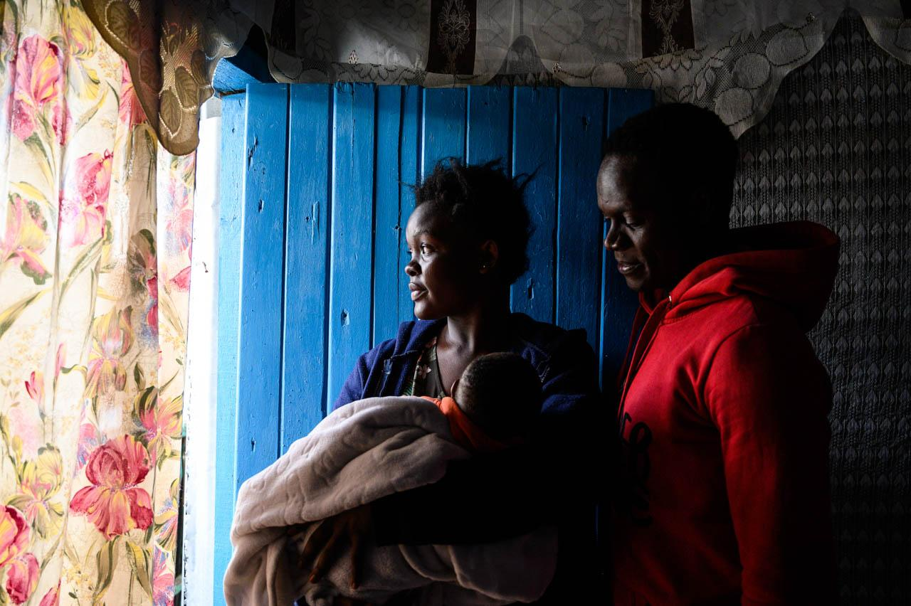 Simon Abukuse, 25, poses for a photograph with his girlfriend Barbra Onganyi, 20, and their two-month old son inside their house in Kibera, Nairobi. Simon, who works as a mechanic and moonlights as a musician, found himself out of work as a result of the government's response to COVID-19, leaving the young family in a very difficult financial situation.