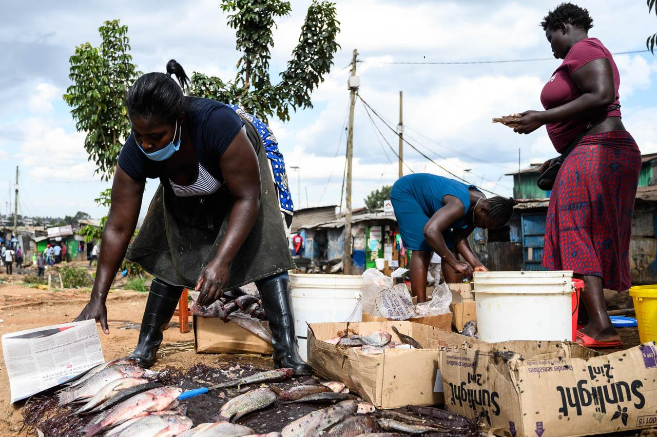 Patricia Adhiambo, far left, and her two assistants race against the clock to prepare the fish they will sell to Kibera residents before the 7pm curfew. Patricia gets her stock of fish from Lake Naivasha, and that arrangement has been strained by localised containment measures. But she managed to overcome all the obstacles and maintain a steady supply, making her business one of only a very few sources of fresh fish in Kibera during the lockdown.