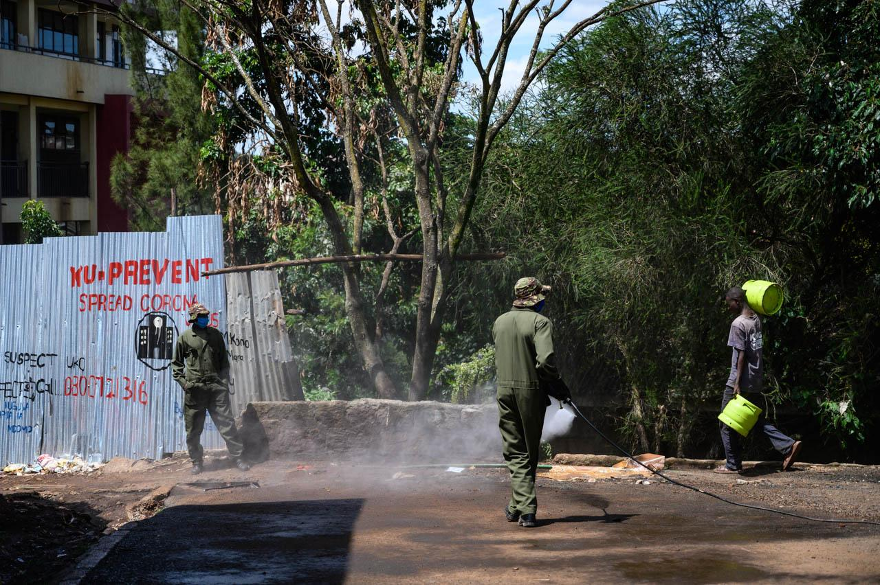 Soldiers from the Kenyan army spray a corridor with disinfectant in a bid to stop the spread of coronavirus in Karanja, Kibera.