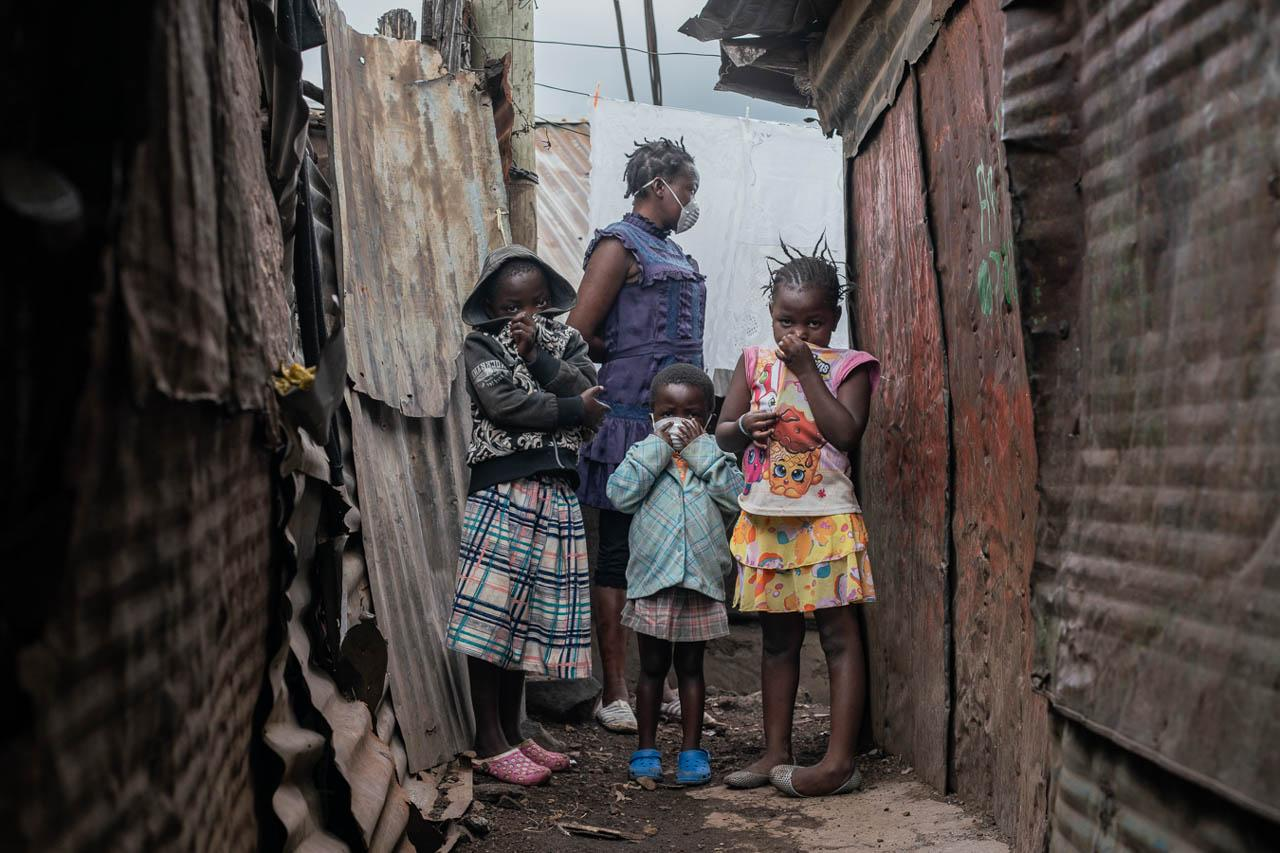 Members of a family wait outside as their house in Kibera is fumigated by soldiers from the Kenyan Army. The fumigation exercise was planned as part of measures to curb the spread of the pandemic.