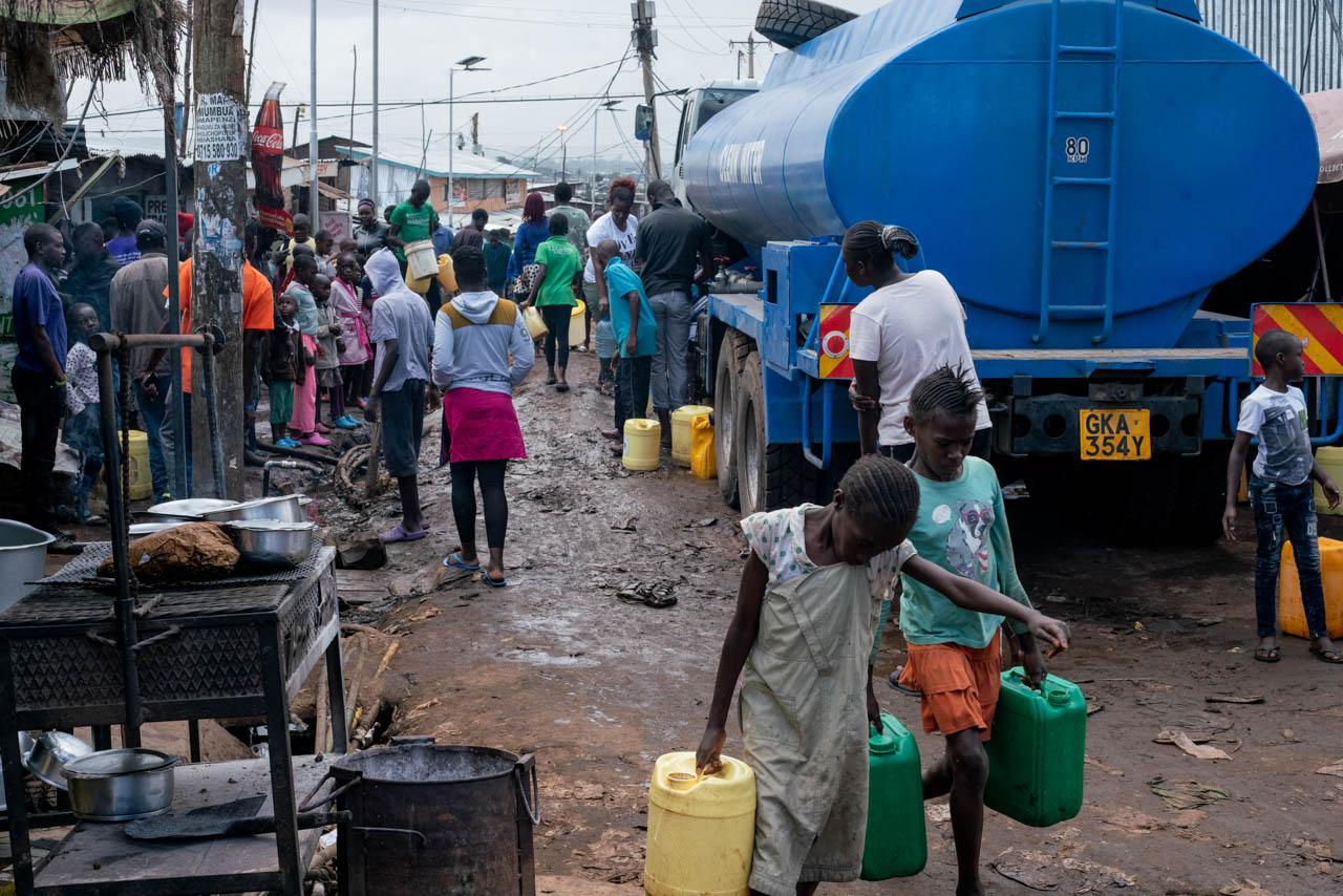 Residents carry jerry cans to and from a water distribution point installed in Kibera by the Kenyan government. President Kenyatta announced the distribution of free water to low-income communities to curb the spread of COVID-19.