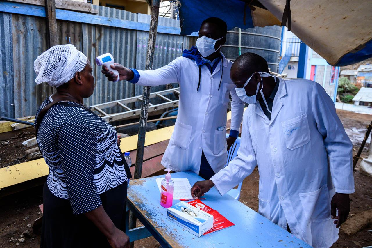 Health workers from Shofco, a local organization, measure the temperature of a woman before granting her access to their facility in Kibera.