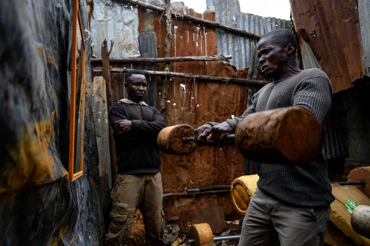 Nicholas Omito, 30, carries a weight as his friend James Aloice looks on. With the current cold Nairobi evenings and imminent curfews making ordinary life difficult, young men are increasingly gravitating towards pastimes they can do in and around their homes.