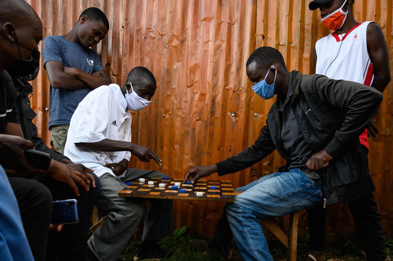 Men finish a last game of drafts minutes before the start of the 7pm curfew in Kibera, Nairobi.