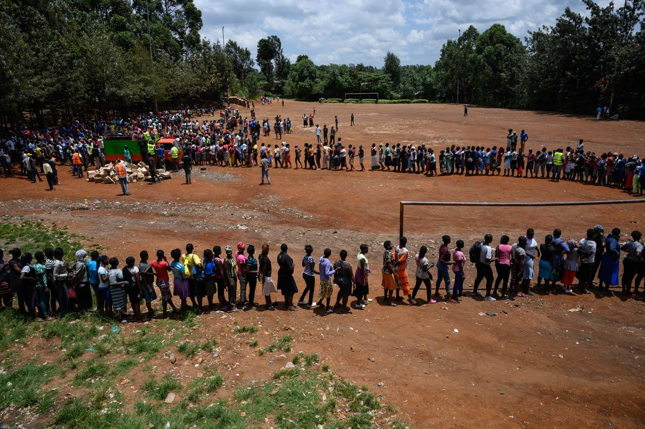 People line up to receive food at a food distribution by Team Pangaj, a Kenyan voluntary group, delivering flour, beans, milk and juice for about 900 people at the Olympic Primary school in the Kibera slum, Nairobi, on April 2, 2020.