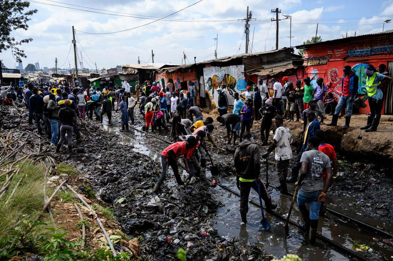 Young people hired by the Kenya National Youth Service (NYS) remove mud from a train track in Kibera, Nairobi, on June 3, 2020.