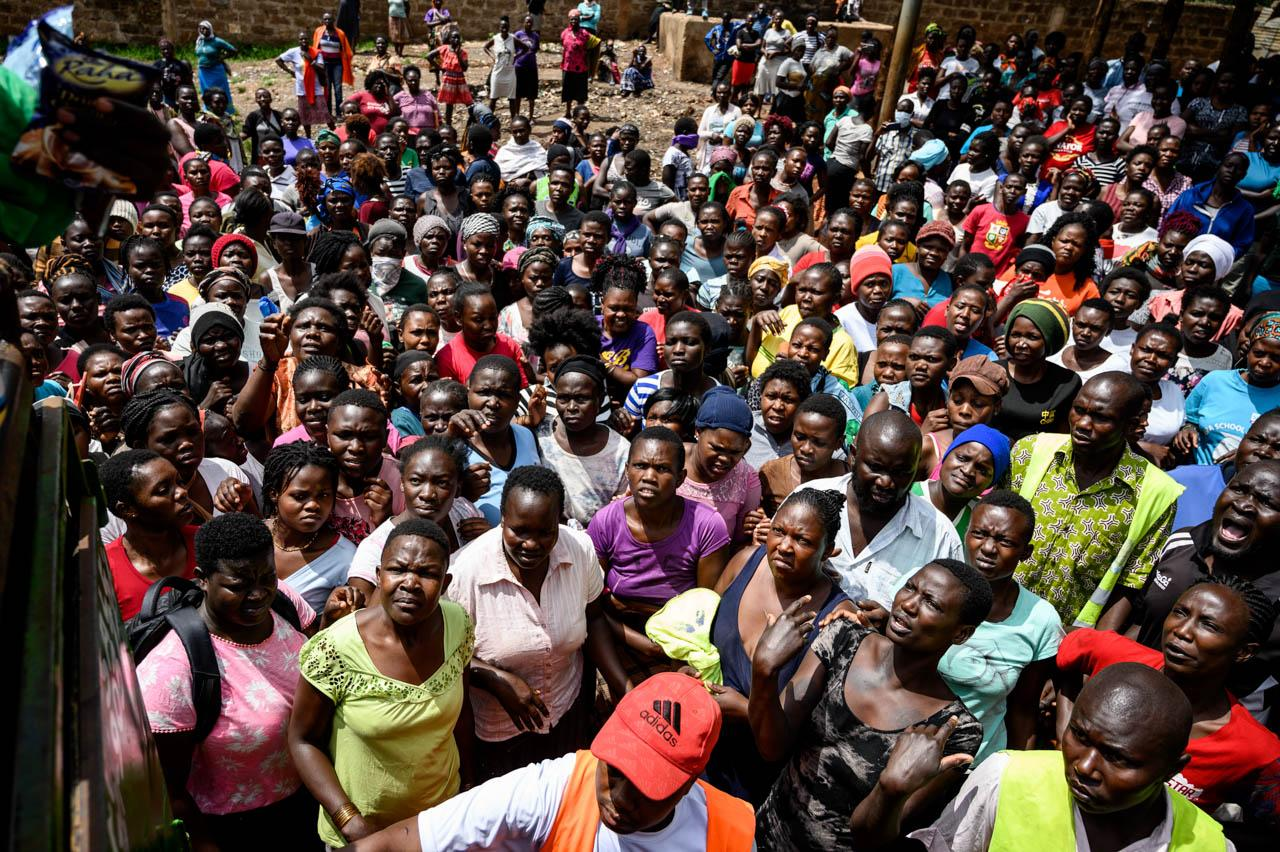 People queue for basic necessities at a food distribution point organised by Team Pangaj, a Kenyan voluntary group which delivered flour, beans, milk and juice for about 900 people at the Olympic Primary school in Kibera, Nairobi, on April 2, 2020.