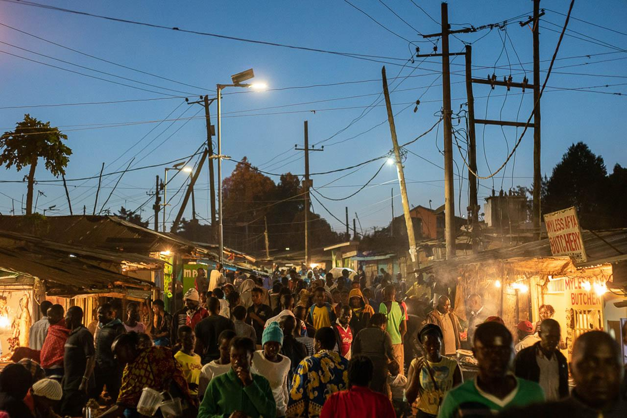 Residents of Katwekera, Kibera, are seen on the streets two hours after the start of the 7pm curfew. Due to the population's size and density, residents have struggled to adhere to social distancing guidelines.