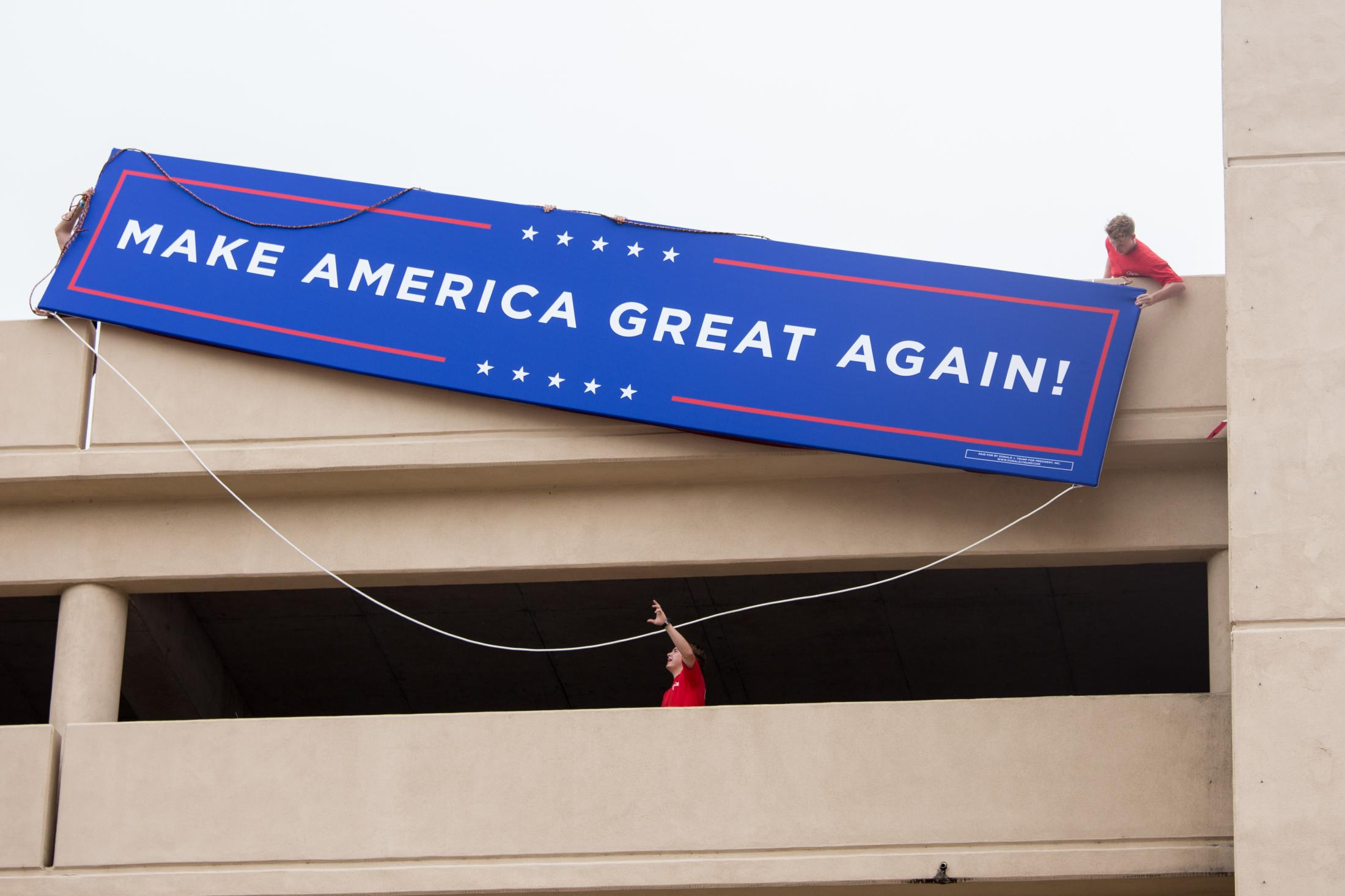 Workers attempt to hang a banner off of the top level of a parking garage near the BOK Center on June 19, 2020, the day before President Donald Trump is holding his campaign rally in Tulsa.