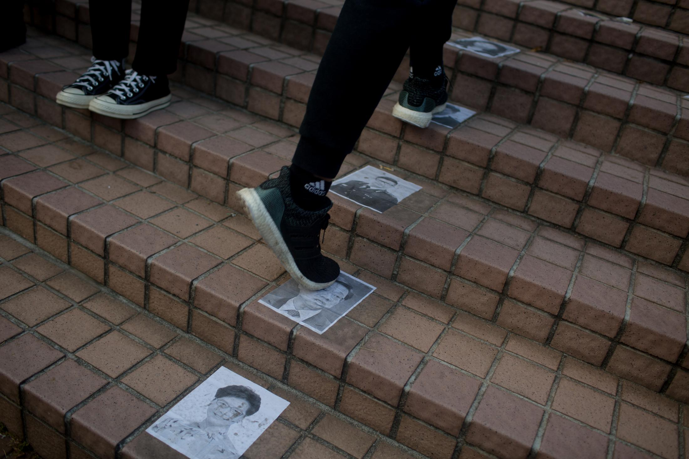 Protesters step on pictures of Beijing friendly leaders on a staircase leading to Edinburgh Place in Central Hong Kong on January 12, 2020.