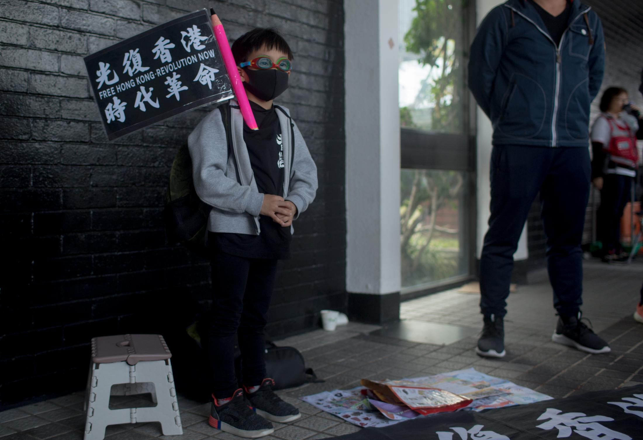 A boy stands at the edge of the Karma to Commies pre-march assembly holding a small pro-democracy flag near his family at Edinburgh Place on January 12, 2020, in Central Hong Kong.