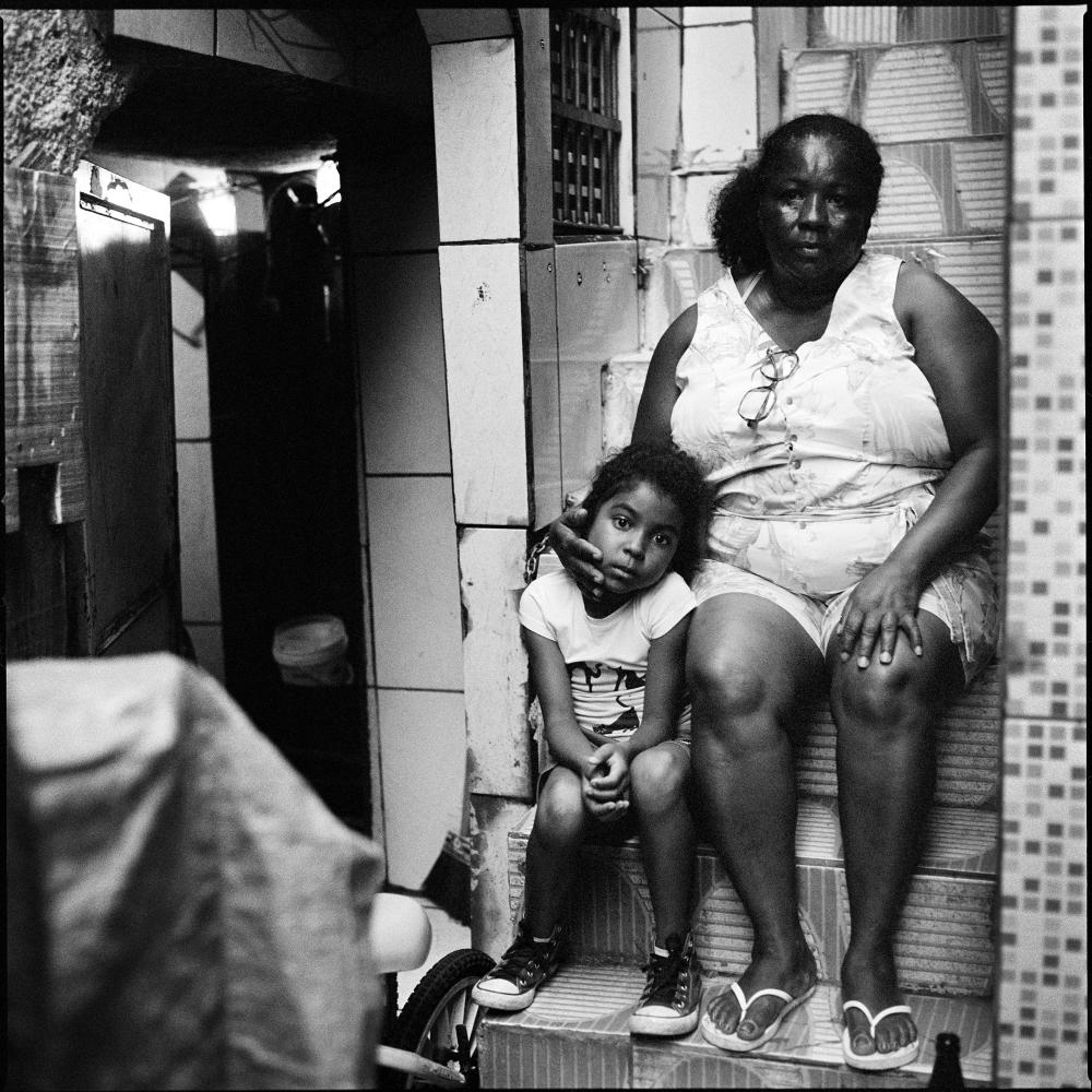 """Jarsilia dos Santos, 51 with her youngest daughter Ashla dos Santos 6, on the side of their """"home"""" basement where some neighbors let her stay with her two children in the Asa Branca favela. Mrs dos Santos, lived for 10 years in Vila Autodromo until she was forced out. Now unemployed, she survives with her children with 171 Reais/34USD a month given to her by the state."""