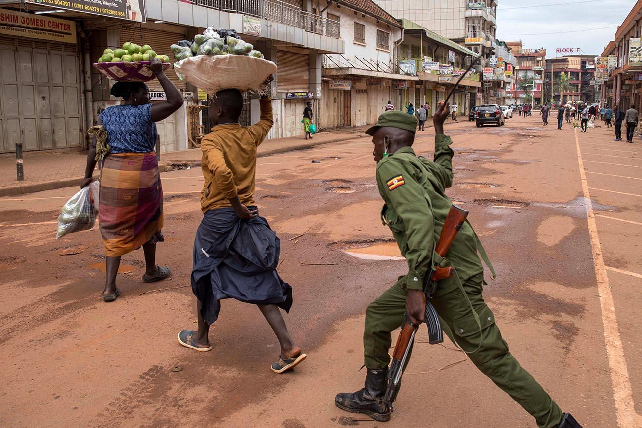 A police officer beating vendors found working on the streets of Kampala defying the presidential directive which asked people to stay home for 32 days and all vendors to work in markets in order to prevent the spread of Coronavirus on March 26, 2020.