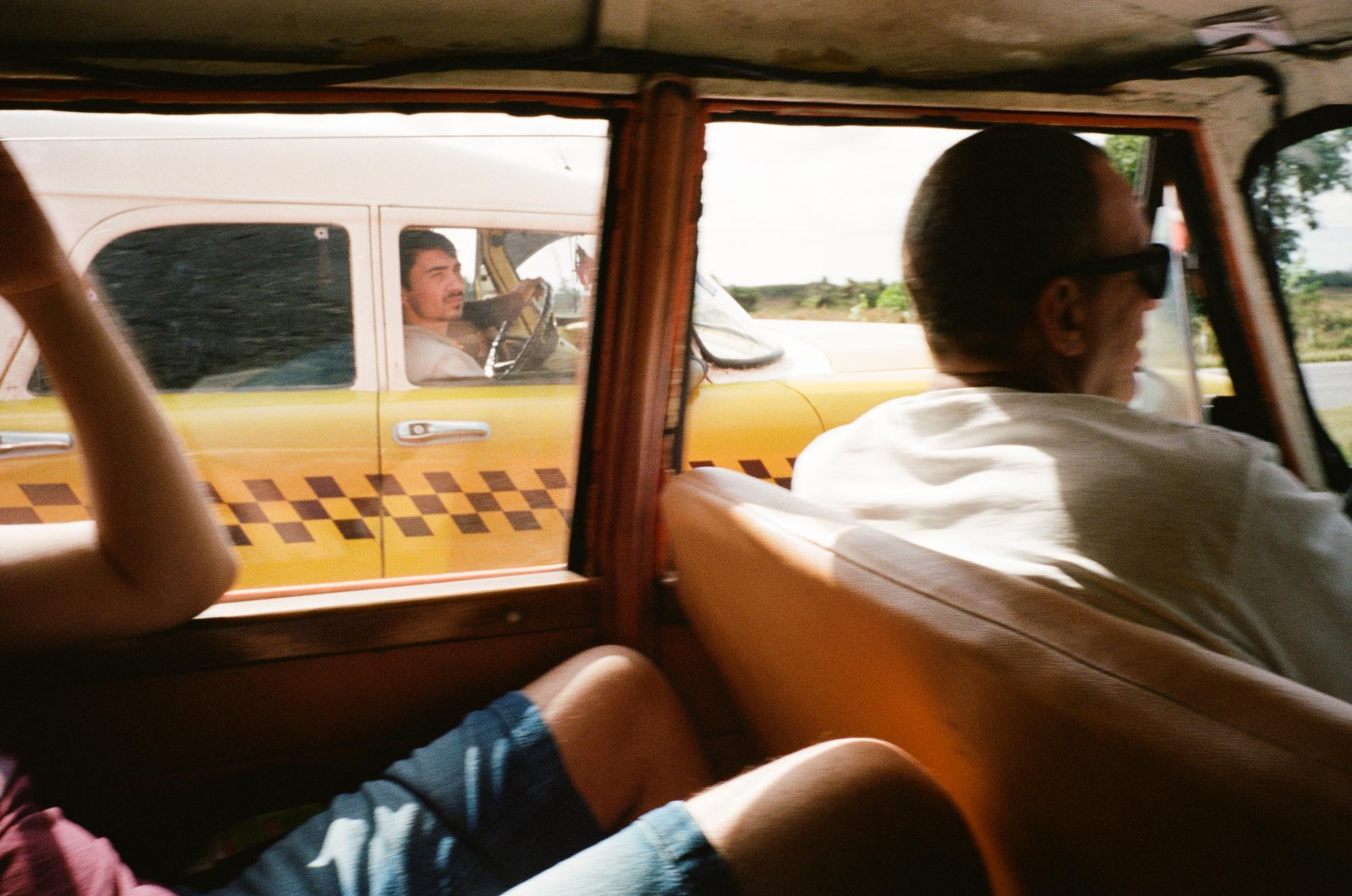 OUTSIDE HAVANA. Autopista Nacional (A4). Westward from Havana to Pinar del Rio. Two cabs full of tourists race each other. Shortly after this image, the two cars pulled close enough on the highway next to each other at full speed.