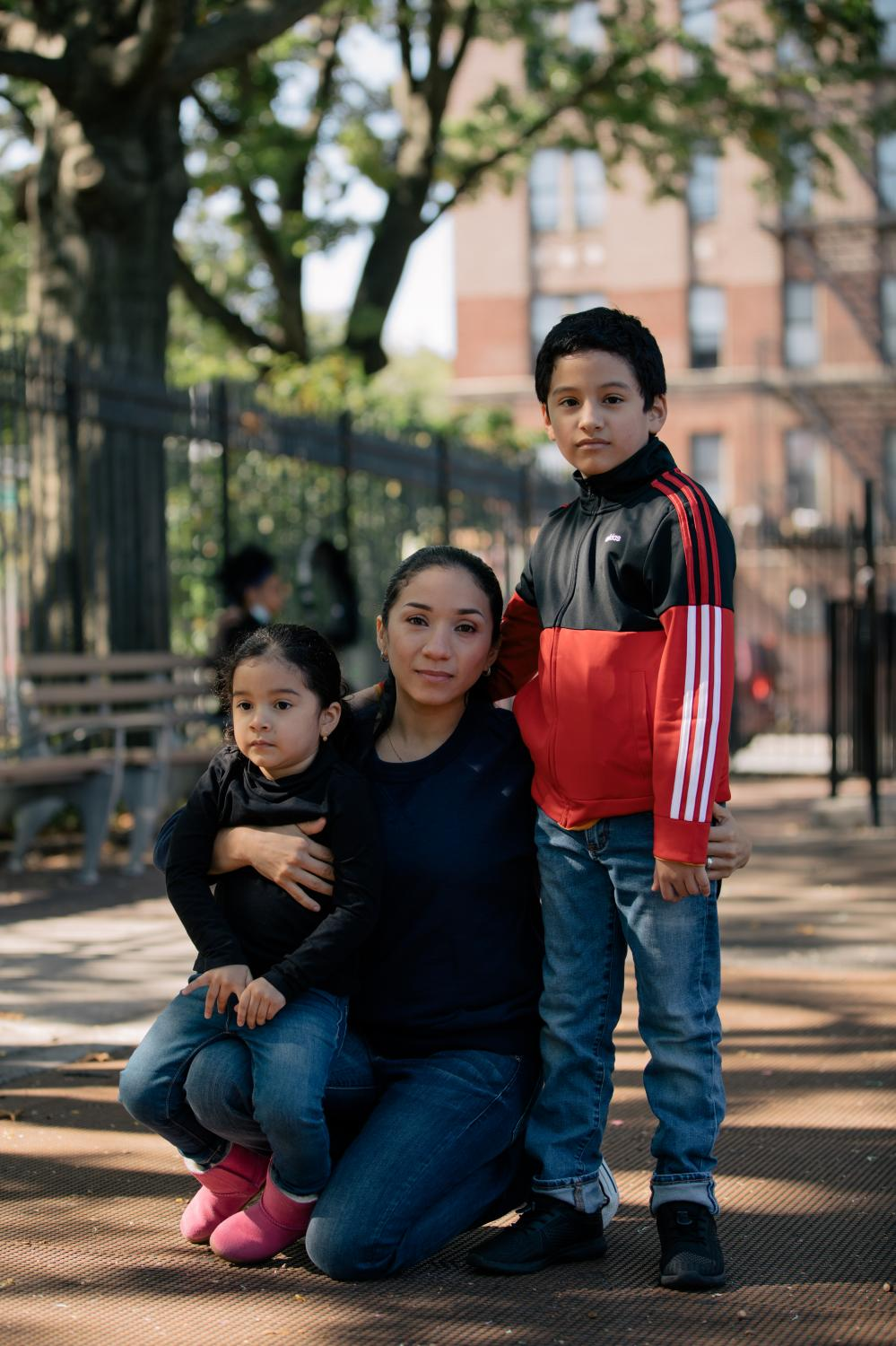 New York City, New York — October 3, 2020: Sylvia Chavez, a parent of two and student at City Tech working toward her associate's degree in construction management, with her two children, with her son Noah Chavez-Giler, 9, and her daughter Allison Chavez-Giler, 3, in Parque de los Niños in the Bronx borough of New York City. As students across the county begin the challenging process of returning to school, many are still hesitant to return to in-class gatherings due to the concern of COVID-19's growing rate of transmission. CREDIT: José A. Alvarado Jr. for The New York Times
