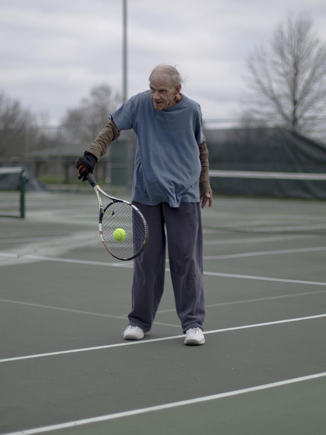 "Noel Heermance, 80, practices tennis by himself March 23, in Cosmo Park. ""If this makes it in the paper, send me a copy,"" Noel said. ""And tell your readers to always practice their backhand (swing.)"""