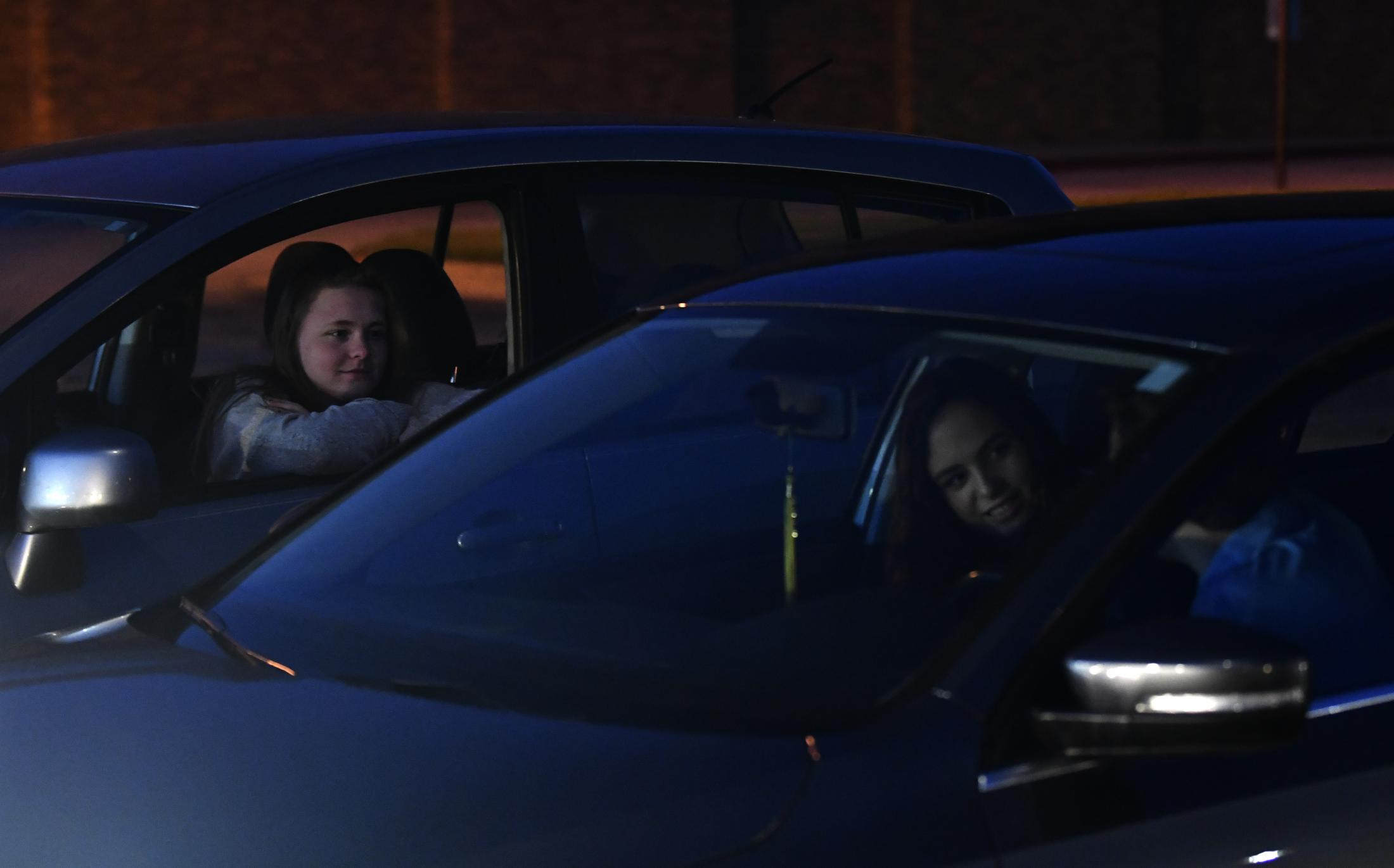 Rock Bridge seniors Madi Polnika, left, 18, Kennedy Robbins, center, 18, and Joseph Gard, right, 18, talk in the school parking lot on April 17, 2020 at Rock Bridge High School in Columbia, Missouri. The three talked about what was happening in their lives now that their year had been cut short due to the COVID-19 pandemic.