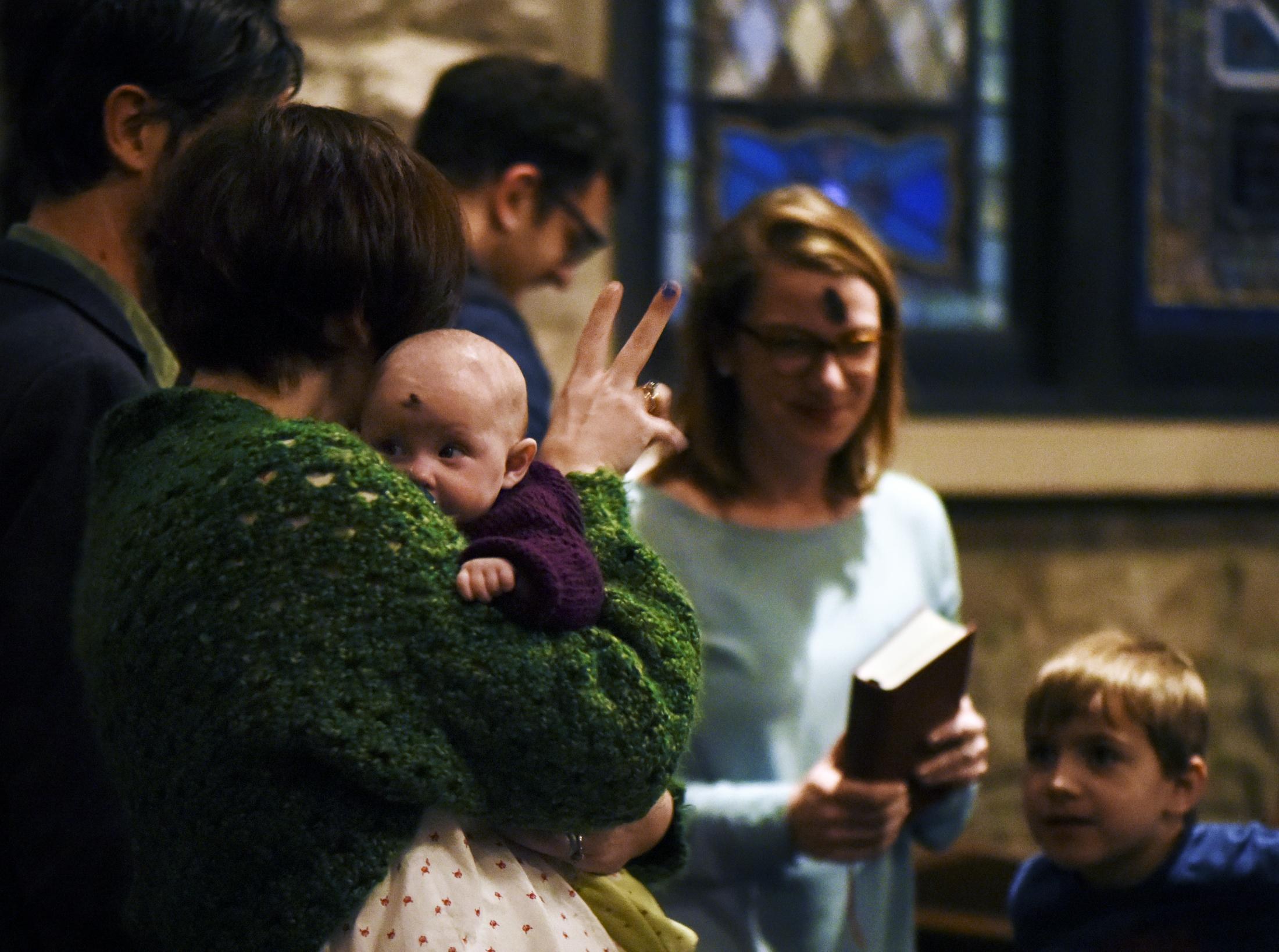 Morgan Owen passes the peace to other members of the congregation while holding her daughter, Hollis Owen, during the Ash Wednesday service on February 26, 2020, at Calvary Episcopal Church in Columbia, Missouri. Ash Wednesday signifies the beginning of Lent for some Christian denominations.