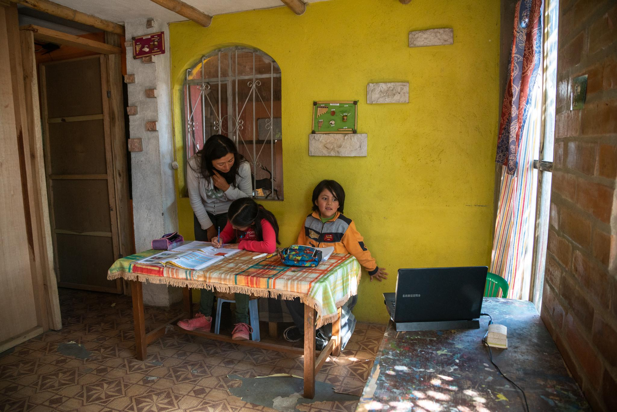 Dina Taco (39) helps her children Suri Laina Aguayo (10) and Jasid Taquiri Aguayo (7) to do their homework, they usually work from 9 to 11.30. They have a computer in which they make academic consultations and listen to music. Jasid Taquiri Aguayo (7) and Suri Laina Aguayo (10) are elementary school students of the Yachay Wasi Intercultural Bilingual Community School. Located south of Quito in Ecuador. They live with her sister Arelí (14), her mother Dina Taco (39) and her father Juan Andrés Aguayo (34). They live in a big house, their grandparents are their neighbors, and they have a big garden full of plants and some trees. Her parents say that at the beginning of the quarantine it was more fun for the children, but nowadays they miss going to school and sharing with their classmates. Dina, the mother, studies Infant Education at a distance, this has given her tools to closely accompany her children's studies during the confinement. She has created routines for children to make better use of time; at 8:30 they do exercises and dance in the patio, until 11:30 they do their homework, then they play and they also collaborate in certain household responsibilities. They are a family with limited financial resources, the Covid19 has left the two parents without work, however, they can lean on their grandparents. They are a family with a broad vision of social work. Photographer: Ana Maria Buitron. Quito, Ecuador. Dina Taco (39) ayuda a sus hijos Suri Laina Aguayo (10) y Jasid Taquiri Aguayo (7) a hacer los deberes de la escuela, suelen trabajar desde las 9 hasta las 11.30. Tienen un computador en el cual hacen consultas académicas y escuchan música. Jasid Taquiri Aguayo (7) y Suri Laina Aguayo (10) son estudiantes de primaria de la Escuela Comunitaria Intercultural Bilingüe Yachay Wasi. Ubicada al sur de Quito en Ecuador. Viven con su hermana Arelí (14), su madre Dina Taco (39) y su padre Juan Andrés Aguayo (34). Viven en una casa grande, sus abuelos son s