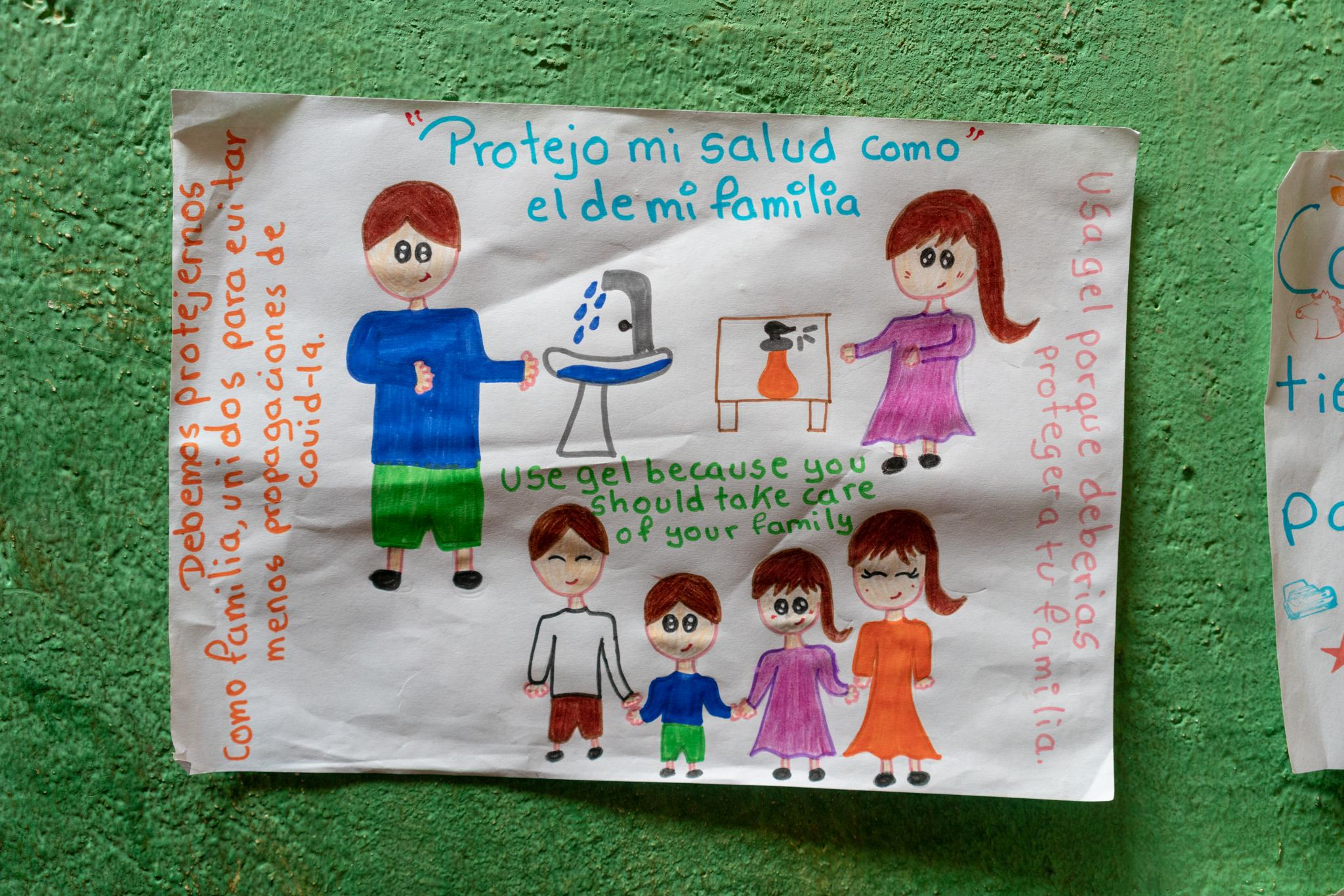 Drawings with messages about how we should act during the Covid19 pandemic. Jasid Taquiri Aguayo (7) and Suri Laina Aguayo (10) are elementary school students of the Yachay Wasi Intercultural Bilingual Community School. Located south of Quito in Ecuador. They live with her sister Arelí (14), her mother Dina Taco (39) and her father Juan Andrés Aguayo (34). They live in a big house, their grandparents are their neighbors, and they have a big garden full of plants and some trees. Her parents say that at the beginning of the quarantine it was more fun for the children, but nowadays they miss going to school and sharing with their classmates. Dina, the mother, studies Infant Education at a distance, this has given her tools to closely accompany her children's studies during the confinement. She has created routines for children to make better use of time; at 8:30 they do exercises and dance in the patio, until 11:30 they do their homework, then they play and they also collaborate in certain household responsibilities. They are a family with limited financial resources, the Covid19 has left the two parents without work, however, they can lean on their grandparents. They are a family with a broad vision of social work. Photographer: Ana Maria Buitron. Quito, Ecuador. Dibujos con mensajes sobre cómo debemos actuar durante la pandemia del Covid19. Jasid Taquiri Aguayo (7) y Suri Laina Aguayo (10) son estudiantes de primaria de la Escuela Comunitaria Intercultural Bilingüe Yachay Wasi. Ubicada al sur de Quito en Ecuador. Viven con su hermana Arelí (14), su madre Dina Taco (39) y su padre Juan Andrés Aguayo (34). Viven en una casa grande, sus abuelos son sus vecinos y tienen un jardín grande lleno de planta y algunos árboles. Sus padres cuentan que al inicio de la cuarentena era más divertido para los niños , pero actualmente extrañan ir a la escuela y compartir con sus compañeros. Dina, la madre, estudia a distancia Educación Infantil, esto le ha dado he