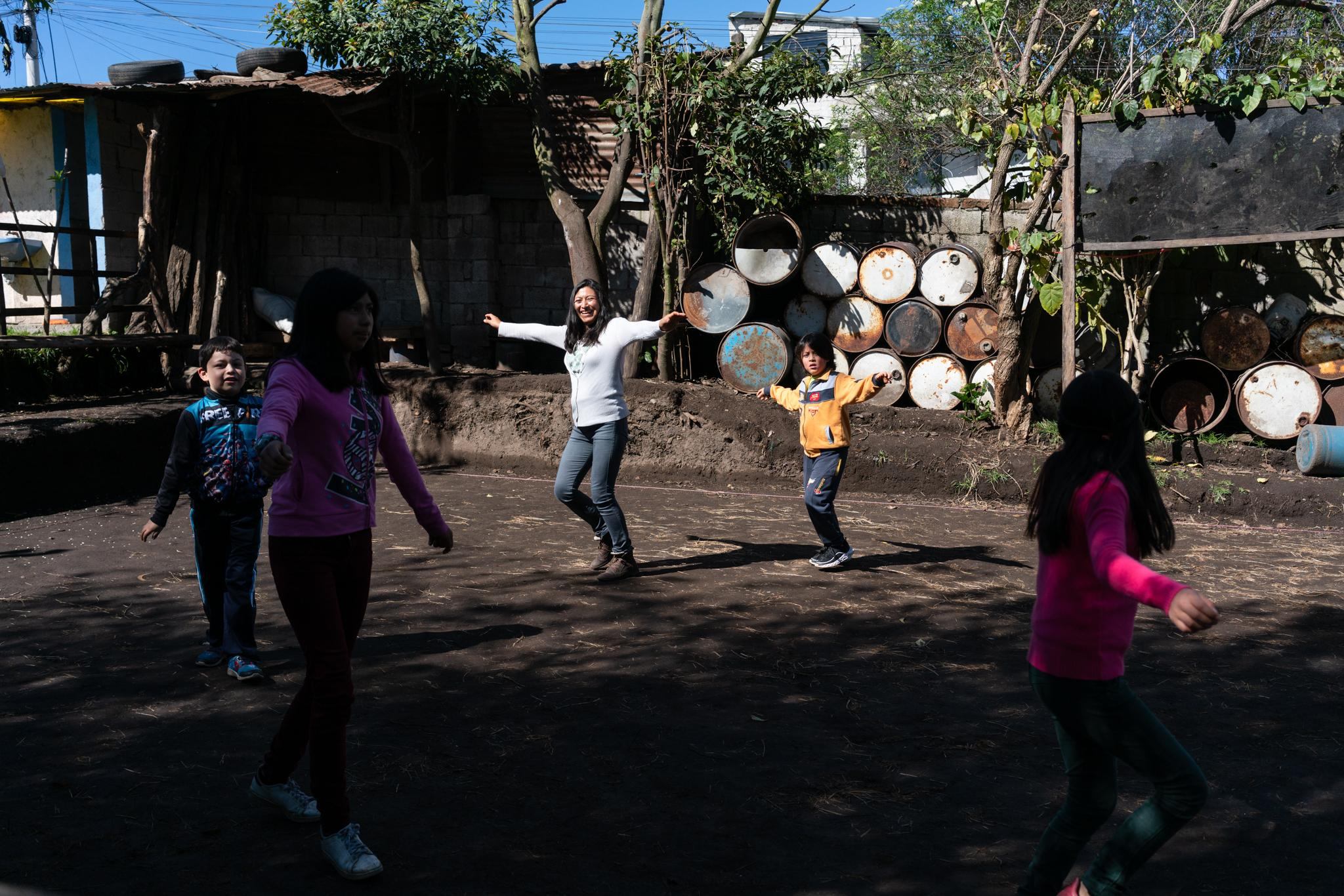 Dina Taco (39) leads a family activity every morning, in which everyone dances and exercises before starting their daily activities. Grandparents (Dina's parents) also participate. Jasid Taquiri Aguayo (7) and Suri Laina Aguayo (10) are elementary school students of the Yachay Wasi Intercultural Bilingual Community School. Located south of Quito in Ecuador. They live with her sister Arelí (14), her mother Dina Taco (39) and her father Juan Andrés Aguayo (34). They live in a big house, their grandparents are their neighbors, and they have a big garden full of plants and some trees. Her parents say that at the beginning of the quarantine it was more fun for the children, but nowadays they miss going to school and sharing with their classmates. Dina, the mother, studies Infant Education at a distance, this has given her tools to closely accompany her children's studies during the confinement. She has created routines for children to make better use of time; at 8:30 they do exercises and dance in the patio, until 11:30 they do their homework, then they play and they also collaborate in certain household responsibilities. They are a family with limited financial resources, the Covid19 has left the two parents without work, however, they can lean on their grandparents. They are a family with a broad vision of social work. Photographer: Ana Maria Buitron. Quito, Ecuador. Dina Taco (39) lidera todas las mañanas una actividad famliar, en la que todos bailan y hacen ejercicios antes de empezar sus actividades cotidianas. Hacen parte de esto también los abuelos (padres de Dina). Jasid Taquiri Aguayo (7) y Suri Laina Aguayo (10) son estudiantes de primaria de la Escuela Comunitaria Intercultural Bilingüe Yachay Wasi. Ubicada al sur de Quito en Ecuador. Viven con su hermana Arelí (14), su madre Dina Taco (39) y su padre Juan Andrés Aguayo (34). Viven en una casa grande, sus abuelos son sus vecinos y tienen un jardín grande lleno de planta y algunos árboles. Sus