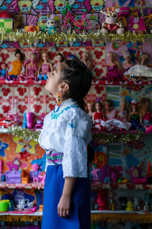 Bianca Ochoa (8), along with her dolls and Barbies. She is wearing her school uniform. Bianca attends the third year of basic education, is a student of the Yachay Wasi Bilingual Intercultural Community Education Center. Located south of Quito. She lives with her maternal grandmother, Blanca Pantoja (52) and with her uncle, since her mother died some years ago. Despite not attending classes in person, Bianca wears her school uniform with pride and excitement. The uniform is the traditional costume of Otavalo, the city where the school principals come from. Bianca enjoys homeworks related to biology, language and traditional dances. The Pandemic affects the economy of her family, however her life at home, during the quarantine, seems to be entertaining. Photographer: Ana Maria Buitron. Quito, Ecuador. Bianca Ochoa (8), junto a su repisa de muñecos y Barbies. Viste el uniforme de su escuela. Bianca Ochoa asiste al tercer año de básica, es estudiante de la Escuela Comunitaria Intercultural Bilingüe Yachay Wasi. Ubicada al sur de Quito Vive con su abuela materna, Blanca Pantoja (52) y junto a su tío, ya que su madre murió hace algunos años. A pesar de no asistir a clases de forma presencial, Bianca lleva puesto en su casa el uniforme de su escuela con orgullo y emoción. El uniforme es el traje tradicional de Otavalo, ciudad de donde provienen los directores de la escuela. Bianca disfruta muchísimo de las tareas relacionadas con biología, lenguaje y con los bailes tradicionales. La Pandemia afecta a la economía de su familia, sin embargo su vida dentro de casa, durante la cuarentena, parece entretenida. Fotógrafa: Ana Maria Buitron. Quito, Ecuador.
